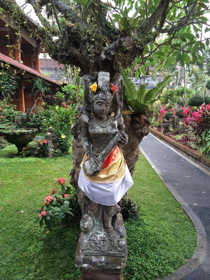 A common sight in Bali ~ to see statues and altars decorated with fabric and flowers.