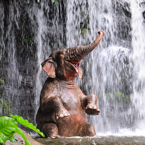 Happy elephant bathes under a waterfall