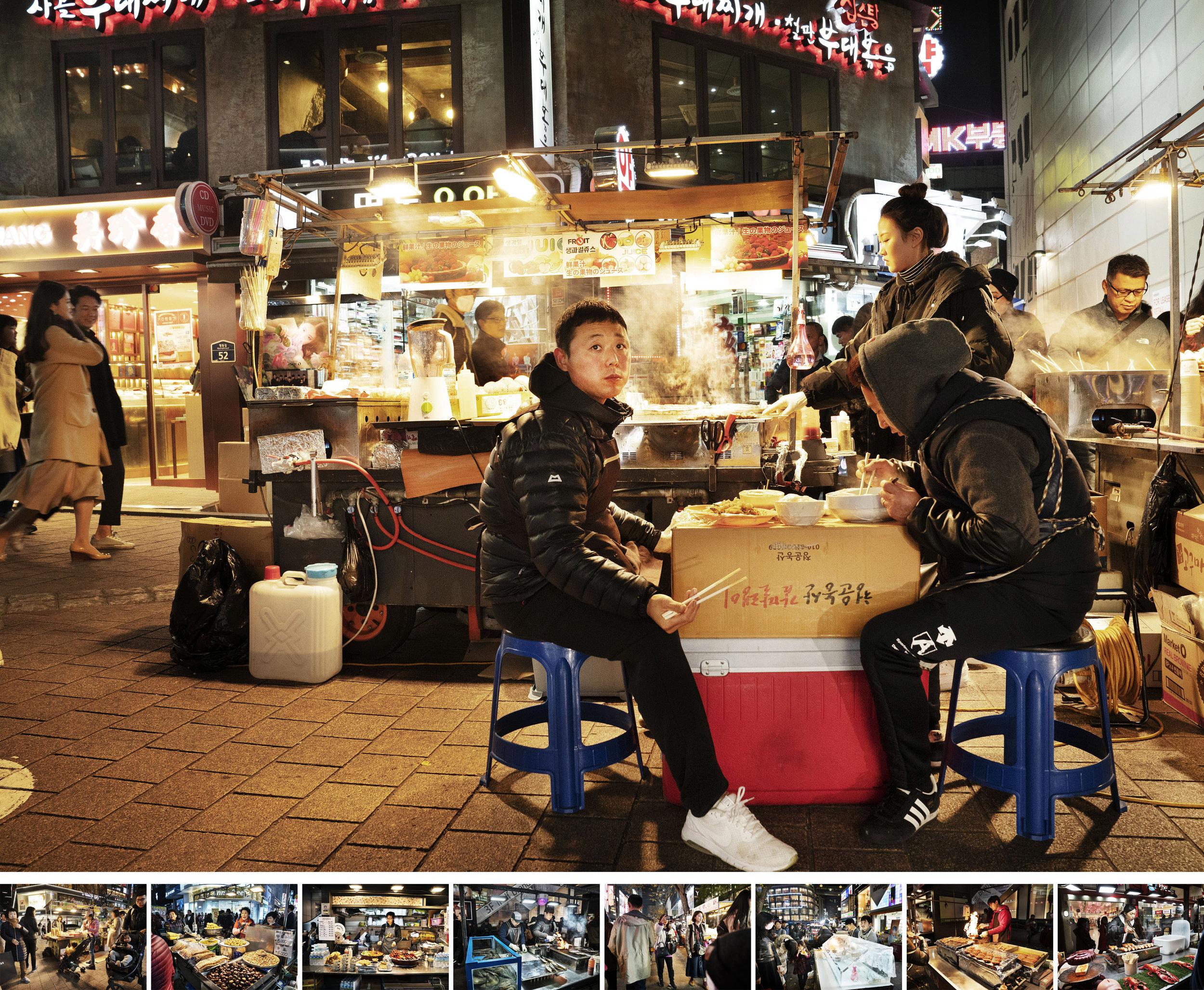 """Seoul Food - フォト・ドキュメンタリー制作物:スチール""""Seoul Food=ソウルの食文化""""は、ロケで韓国を訪れた際に明洞で見つけた、夜のフードマーケットの様子を記録したドキュメンタリー。カラフルなファッションのお店が立ち並ぶエリアの中で、フードマーケットは多くの人々を引き寄せ、独特の存在感を放っていた。あらゆる種類の食べ物が溢れ、蜜の壺に群がる蜂のように、人々が吸い寄せられていく。楽しい夜が過ごせる場所だ。"""