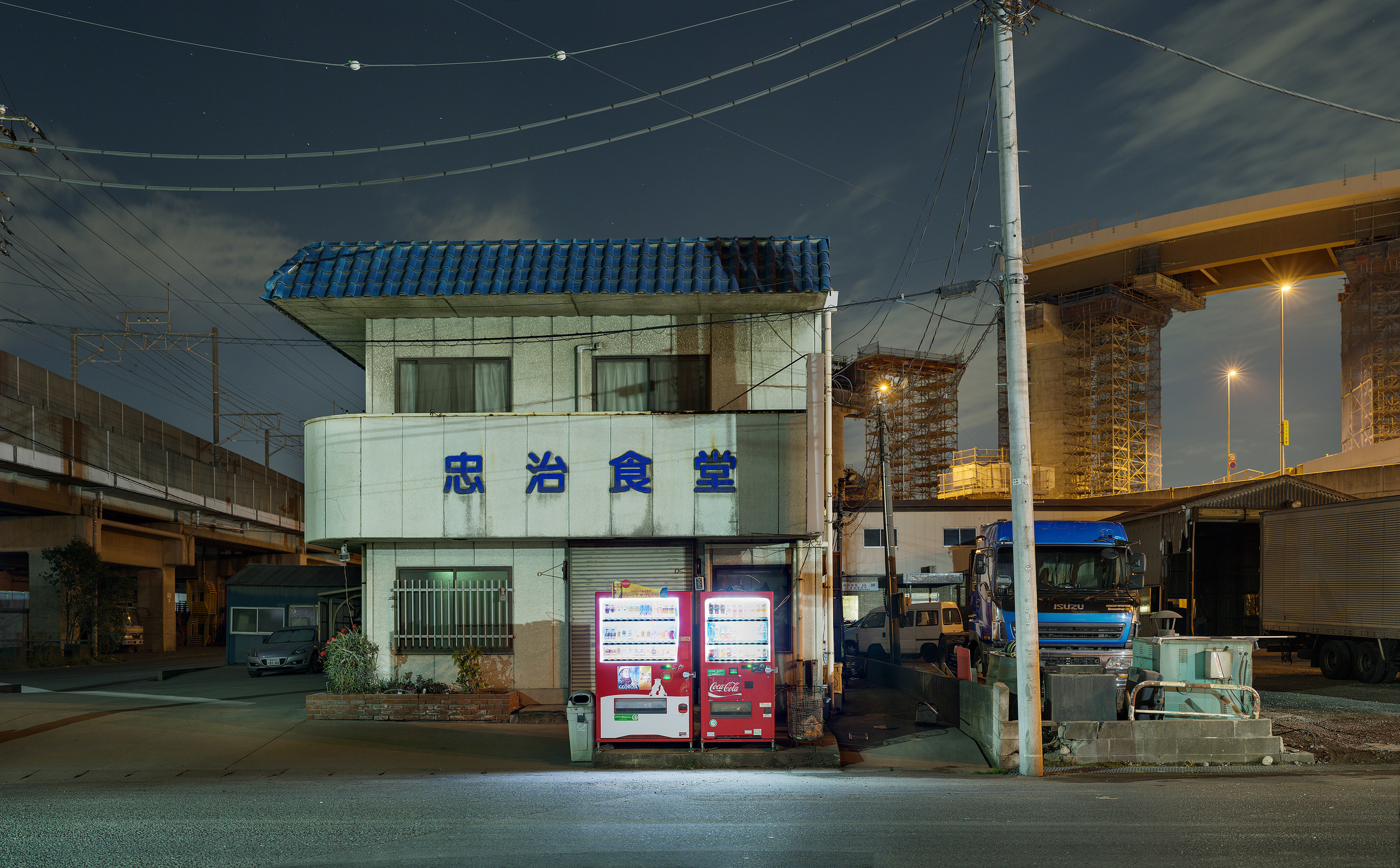 "Tokyo Industrial - 写真展展示作品""Tokyo Industrial=工業都市としての東京""を撮影し始めた当初は、眠らない街の夜の神秘と世界最大の都市の活力源となっている工業の巨大な力に魅了されていた。しかし夜の闇に潜む風景を探しながら撮影を続けていく中で、自分が捉えているものの正体は人間を支配し破壊しようとしているケダモノであることに気がついた。この殺風景なディストピアは、人類が産業の発展の末に辿り着いた世界である。その業績、進化、生み出す力は素晴らしいものであるが、なお成長を続ける世界は人類の最終的な崩壊が始まっていることを示唆してもいる。撮影中のある早朝、4時という時間にも関わらず連日24時間休みなく稼働を続ける化学工場の唸りと噴煙に包囲された自分が向かい合っているのは地球の消滅のサインであることに気付き、恐怖を禁じ得なかった。人の持つ征服欲、創造欲、そして支配欲は止めようがないことを恐ろしく思う。それらはこの地球を私たちが実際には望んでいない形の世界に変えてしまうだろう。そしてそれは取り返しがつかない。自分たちの作り上げてきたものの巨大さを享受する自分と、その意味するところに恐怖を感じる自分がいる。"