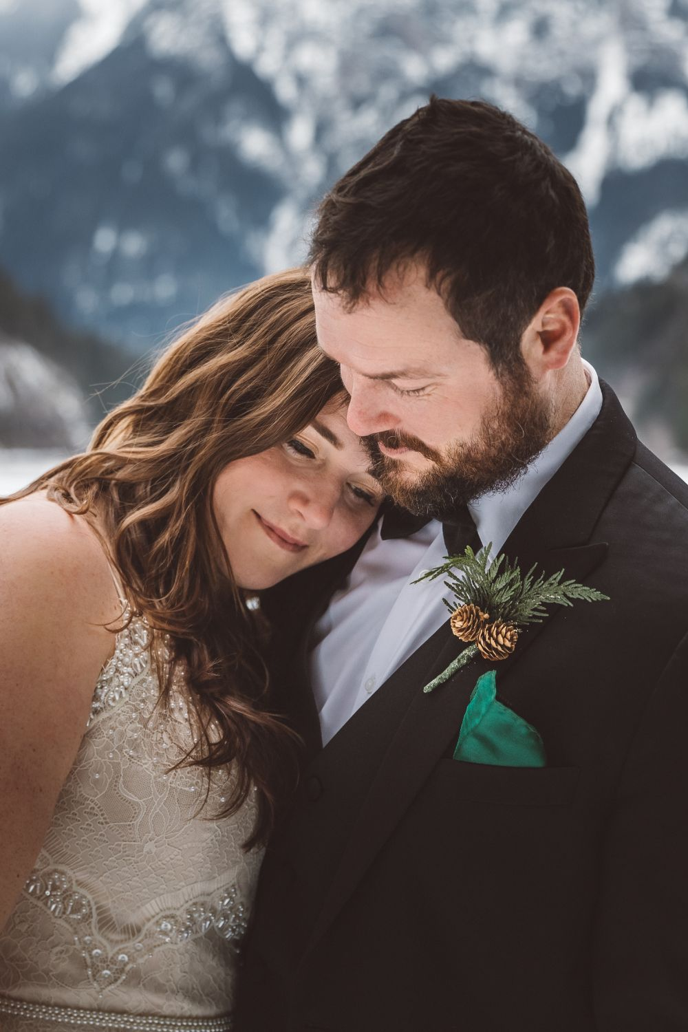 bride-snuggling-groom-snowy-mountains