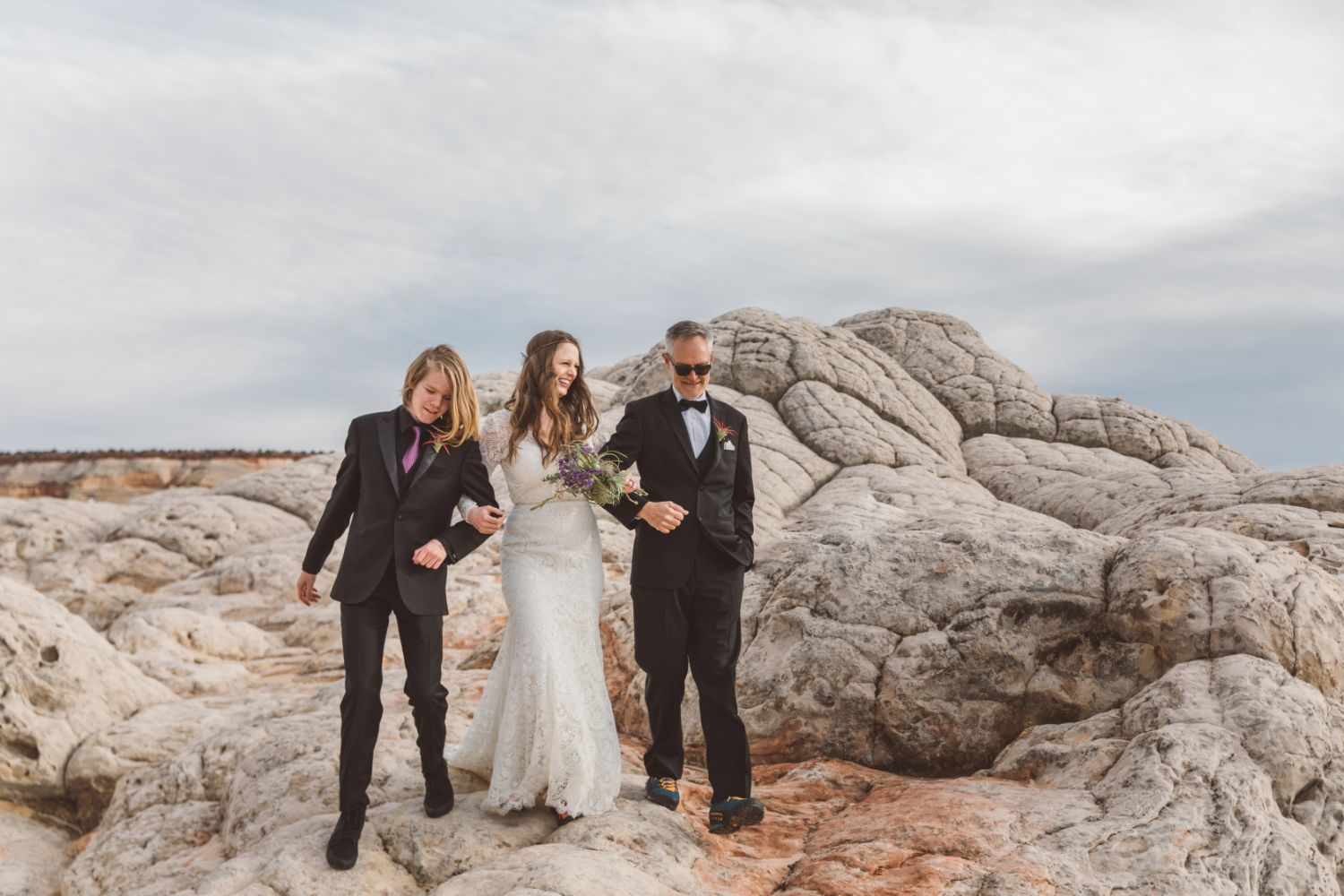 bride-walks-over-sandstone-with-friends