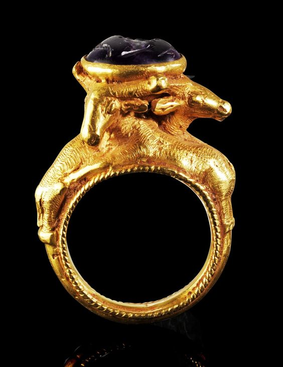 Greek Gold and Amethyst Ring, 1st Century BCRing with 3 gazelles on the hoop holding an oval mounting with a carved amethyst depicting a female draped bust with stephané and cornucopia and corn ear..jpg