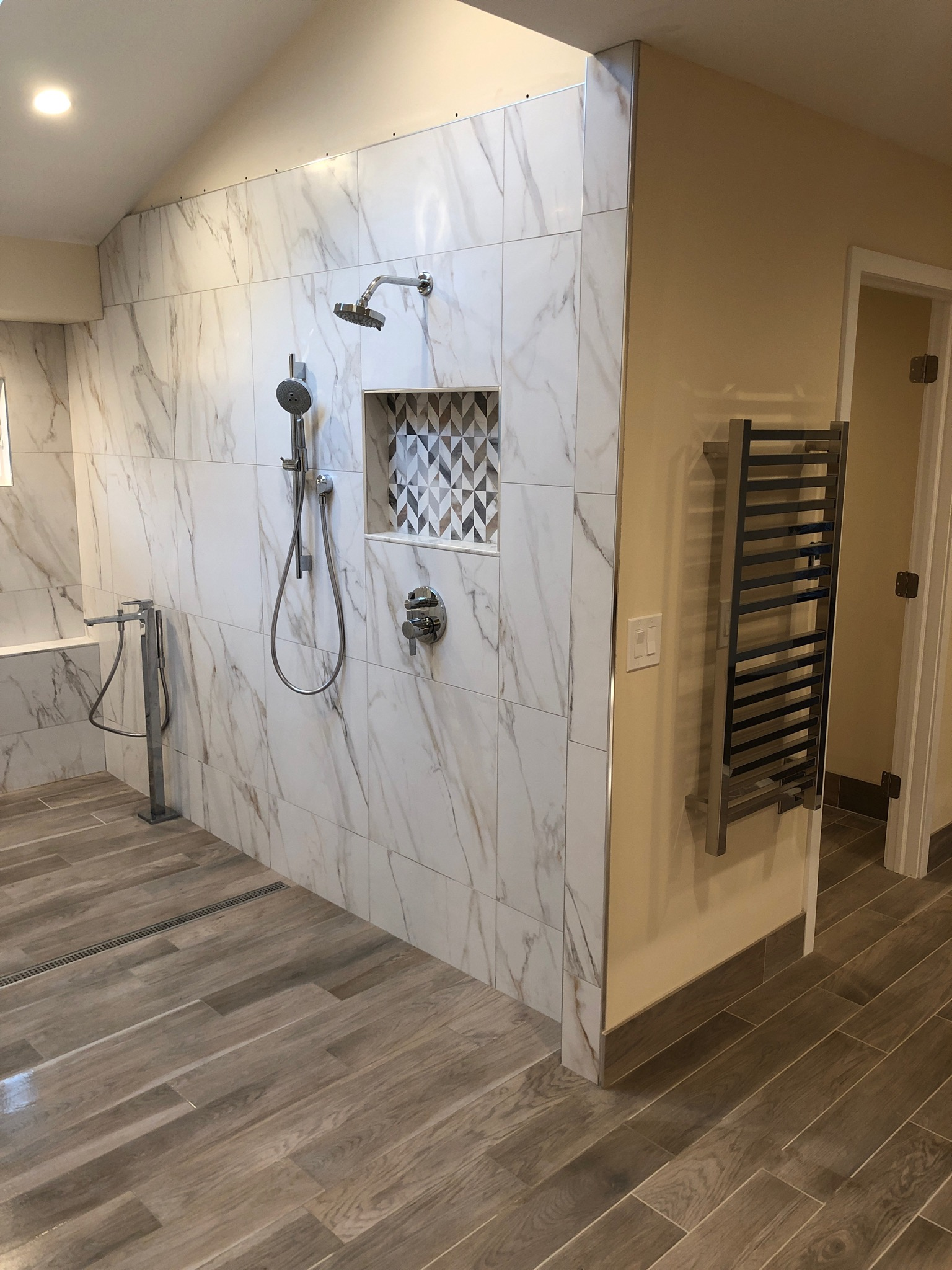 Custom towel warmer and shower controls, installed and ready for use.
