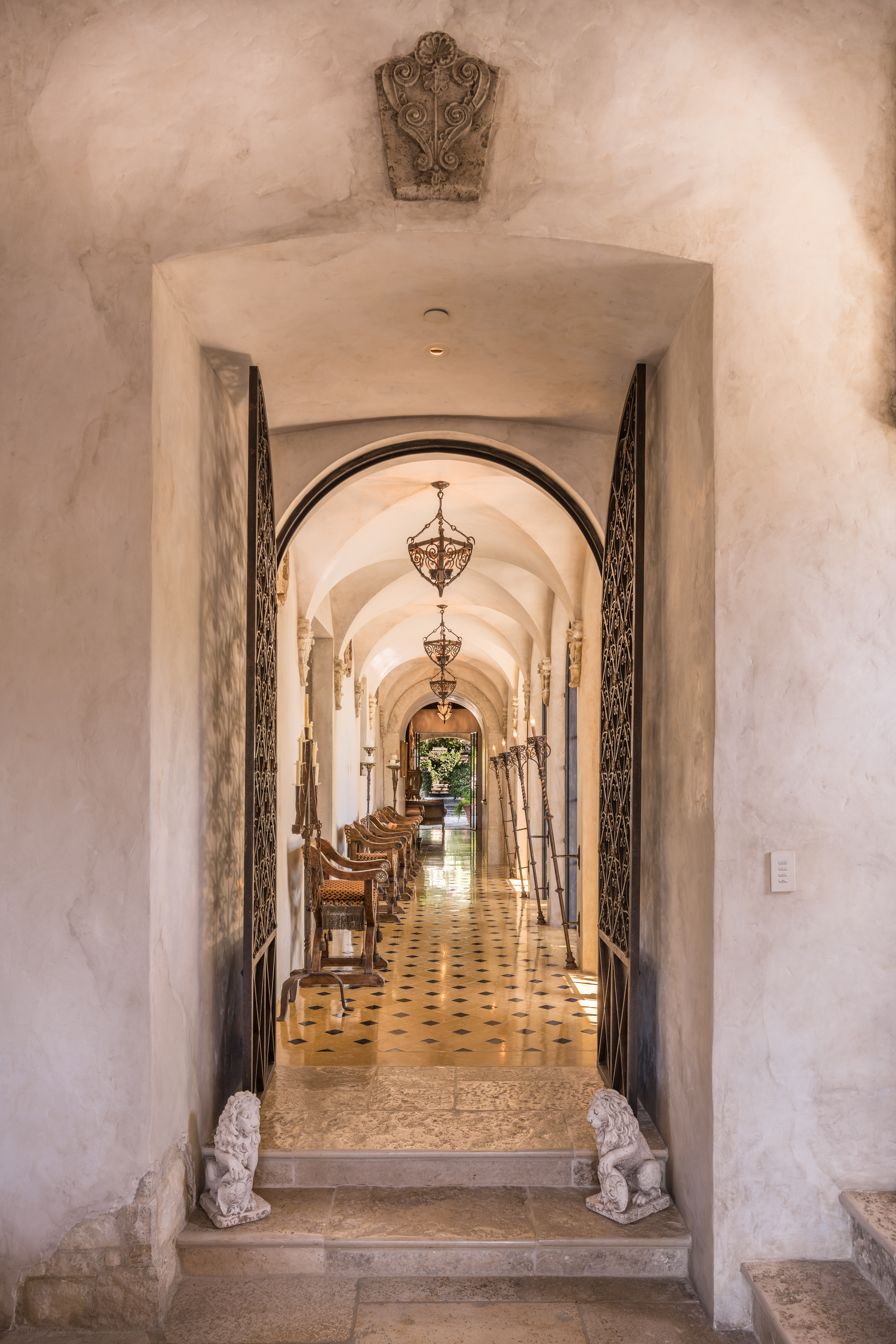 The grand entrance is thoughtfully lined with iron details and French doors that let in abundant light.