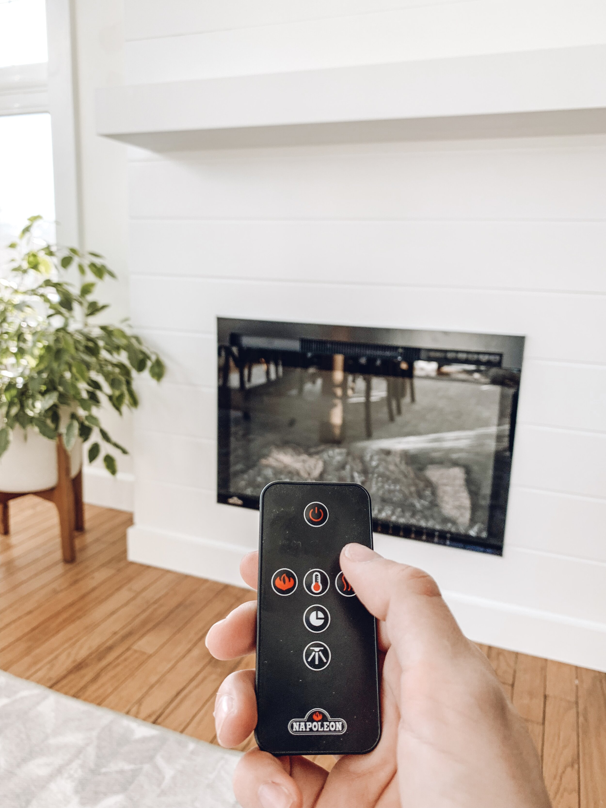 a hand holding a remote for an electric insert for a fireplace