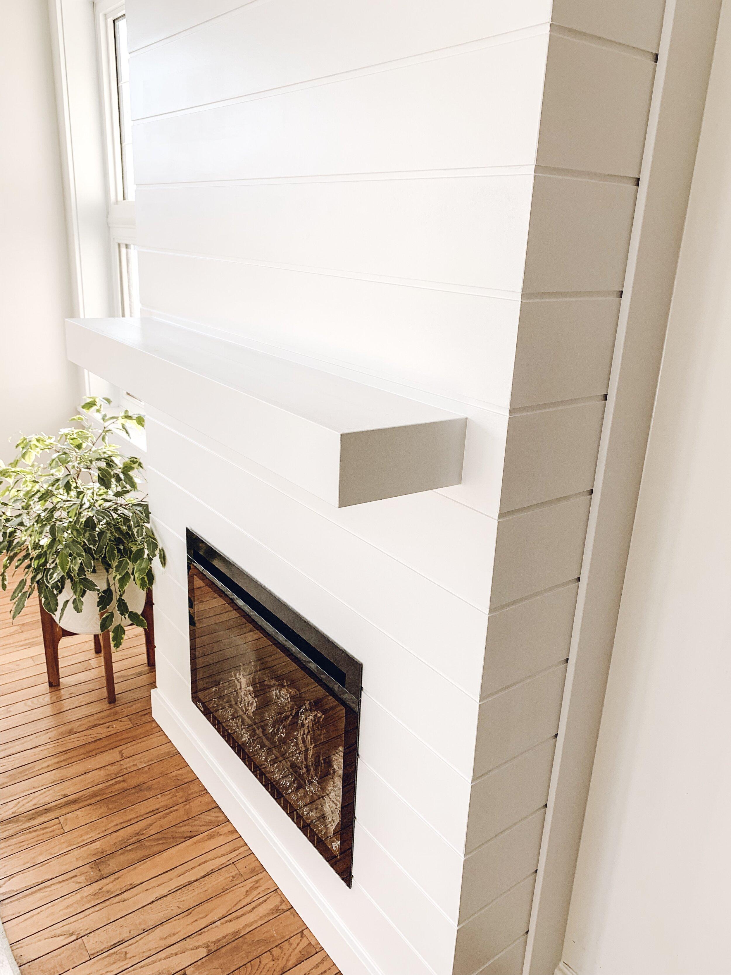 a white shiplap mantel on a fireplace