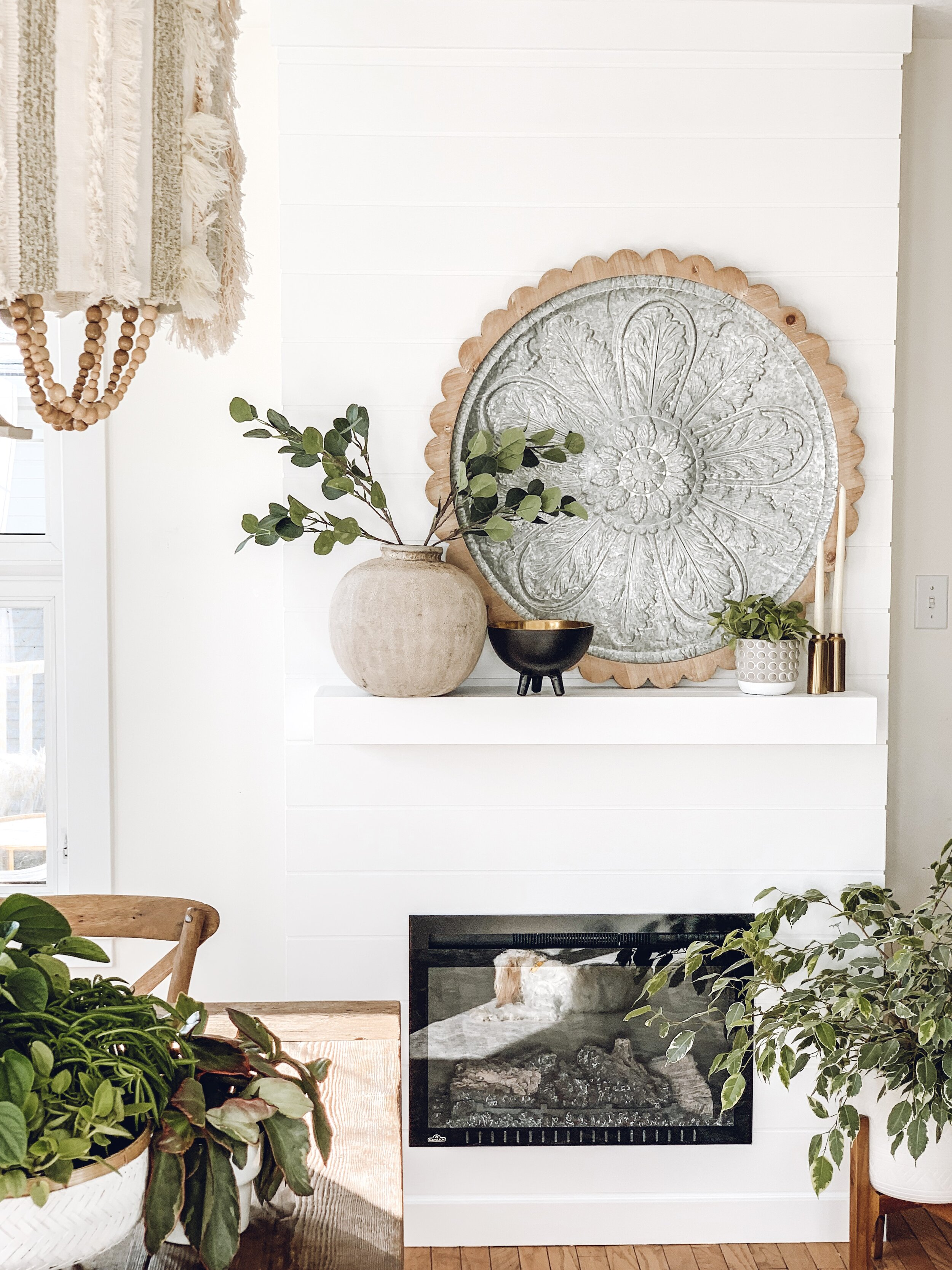 a decorated mantel on a white shiplap fireplace