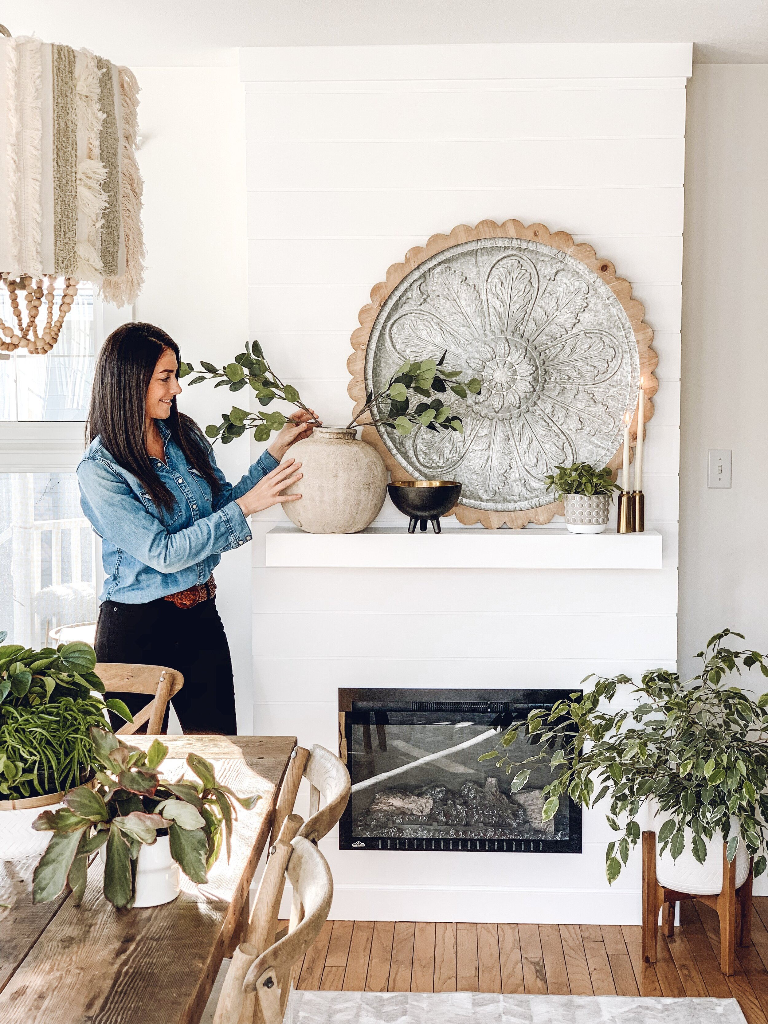 a woman holding some stems in a vase for an electric fireplace