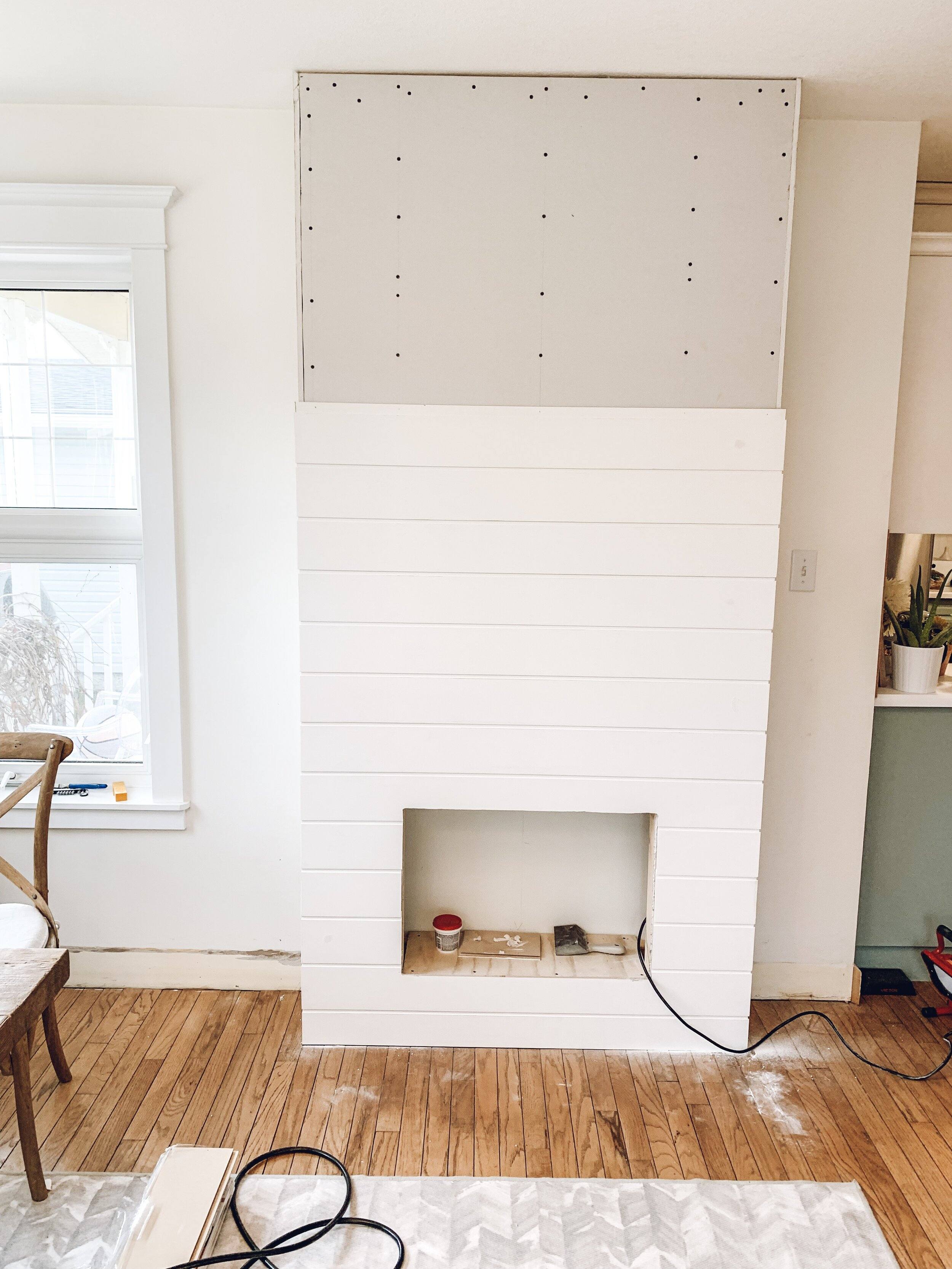 shiplap being applied to an electric fireplace DIY