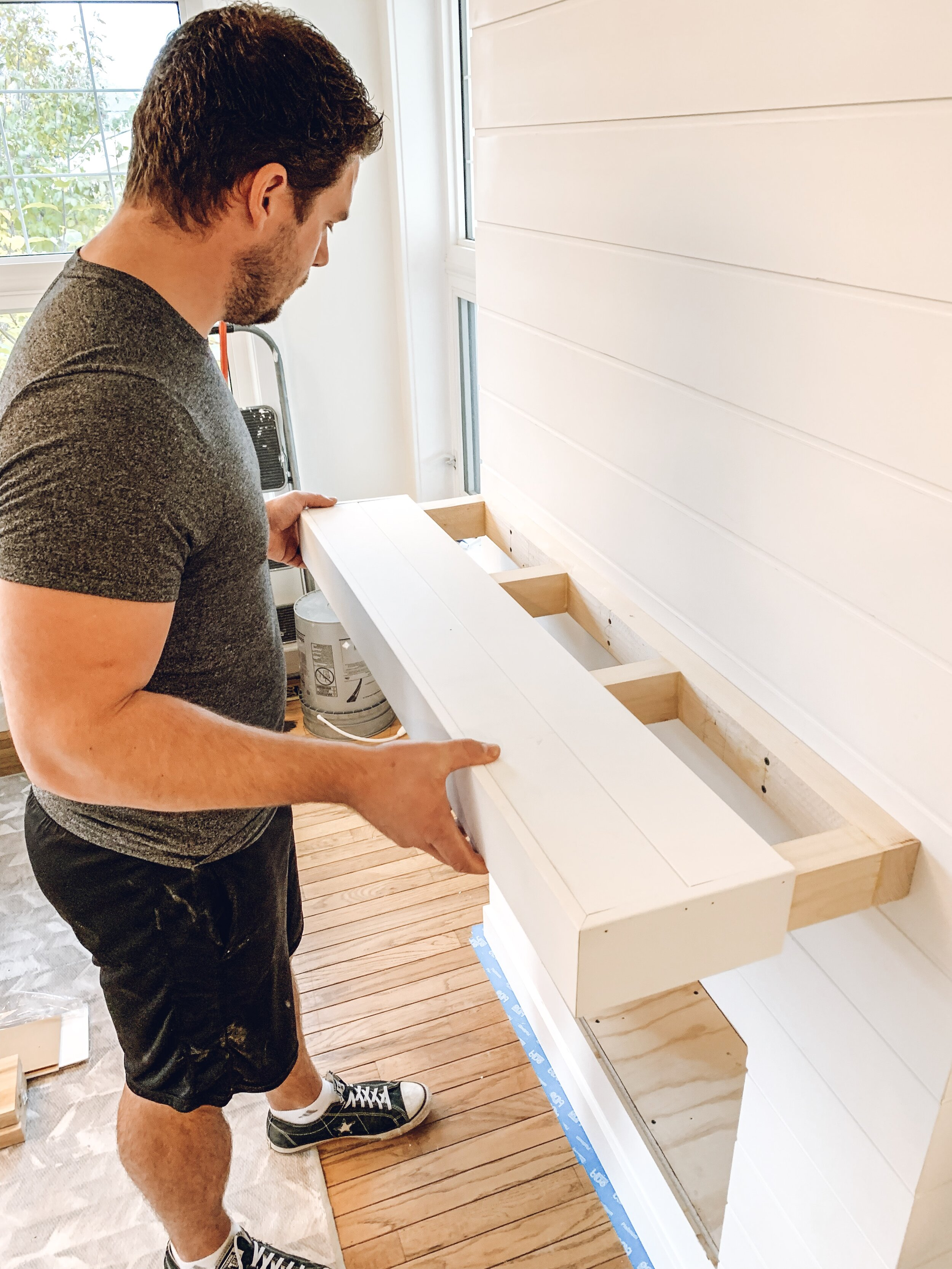 a man adding a mantel covered in shiplap to a electric fireplace