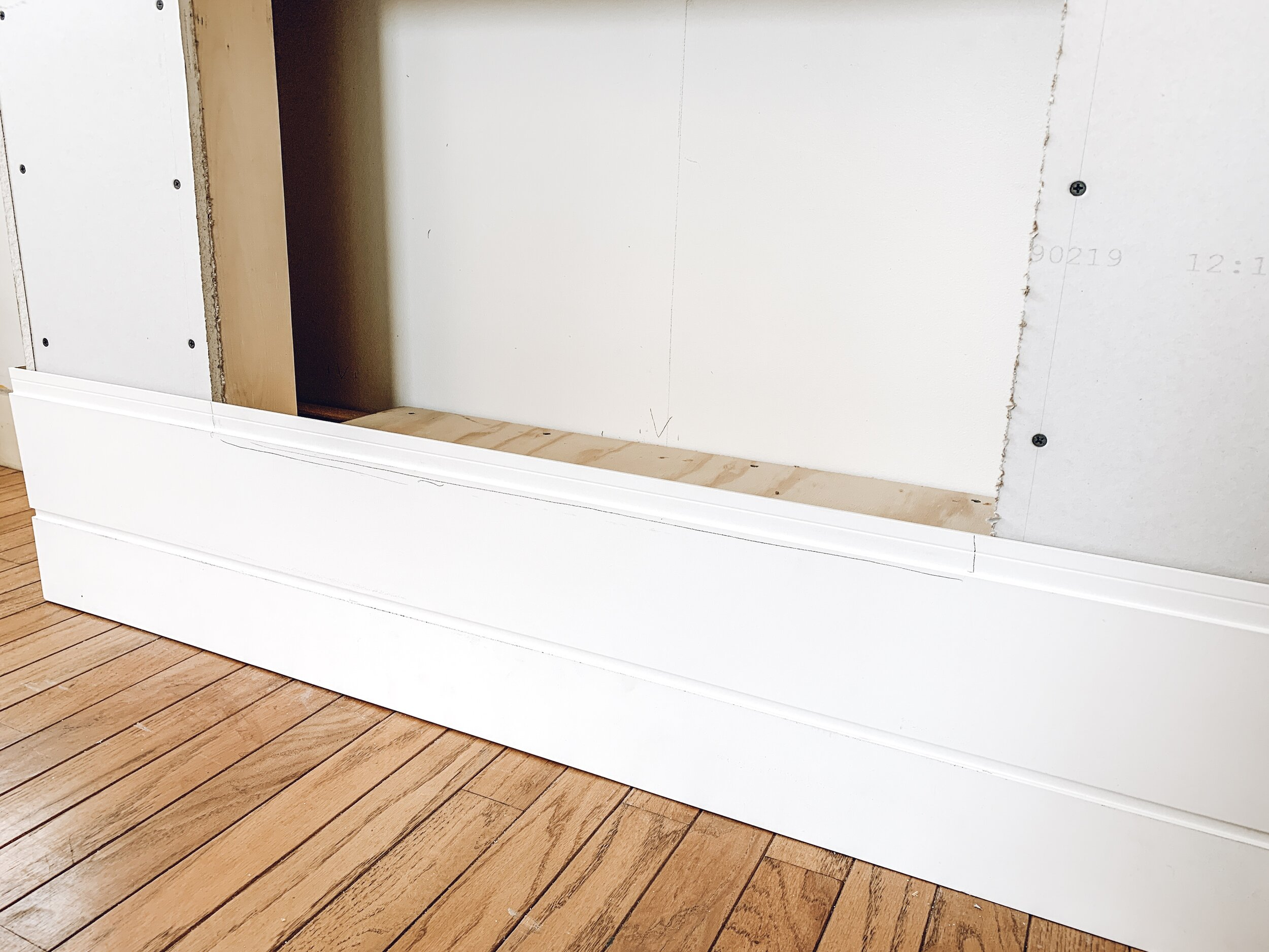 a photo of the first strips of shiplap being measured for a shiplap fireplace