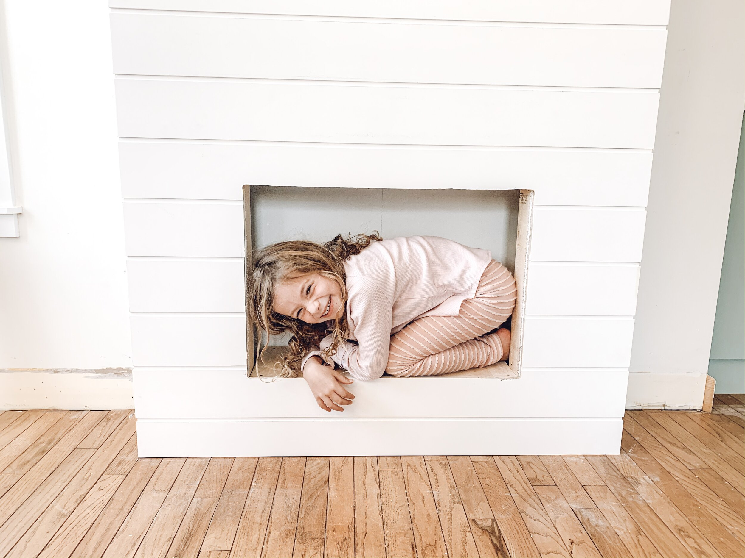 a little girl in the hole for an electric insert in a fireplace covered in shiplap