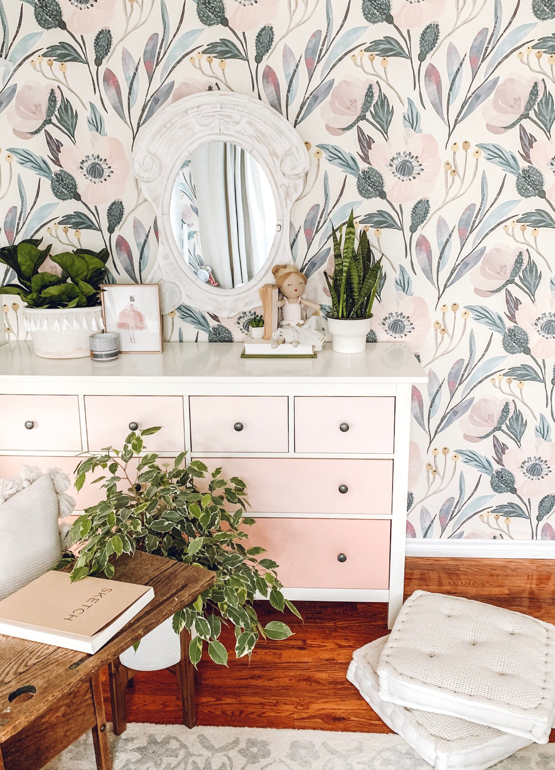 this is a photo of floral removable wallpaper in a little girls room with a pink dresser