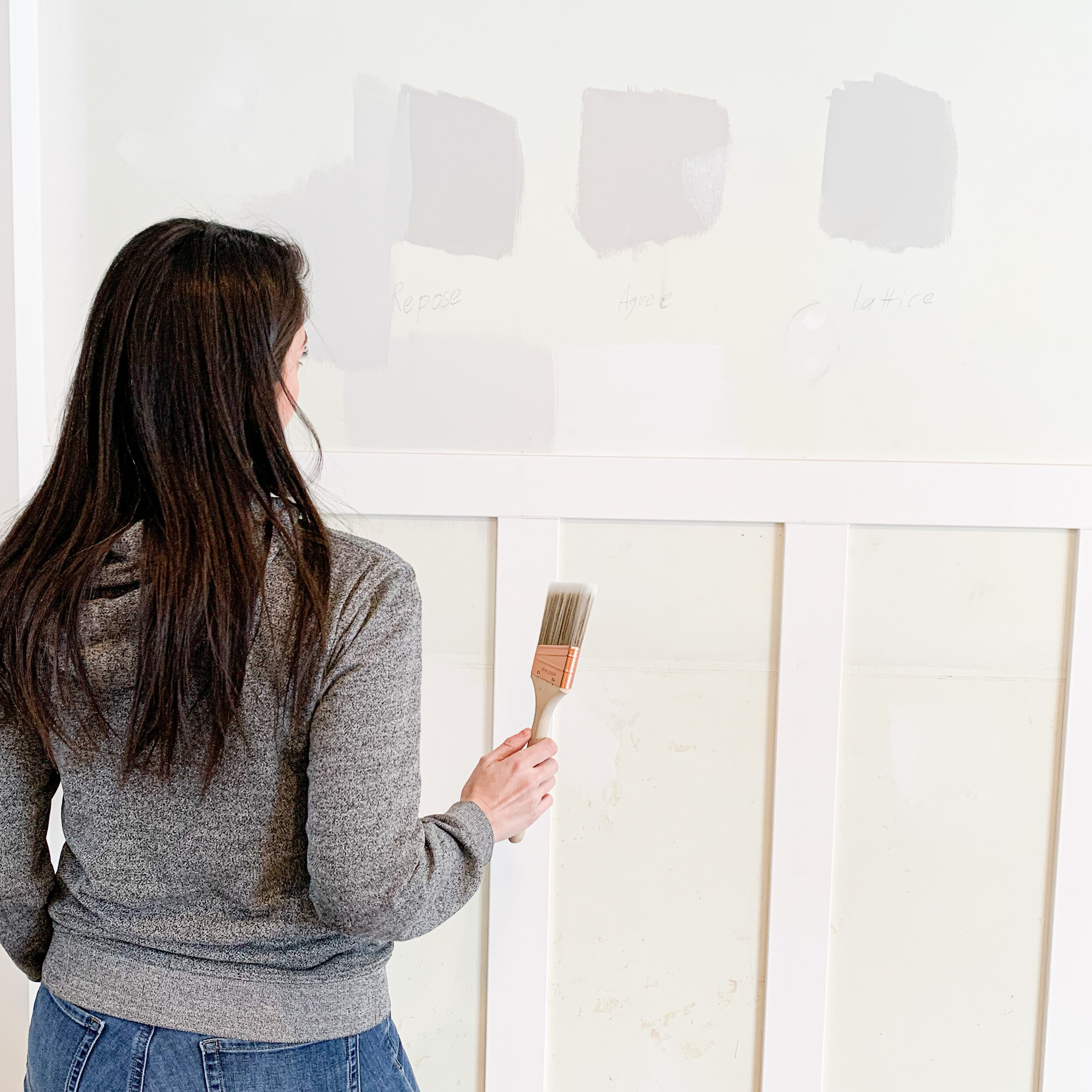 a woman painting grey swatches on a wall