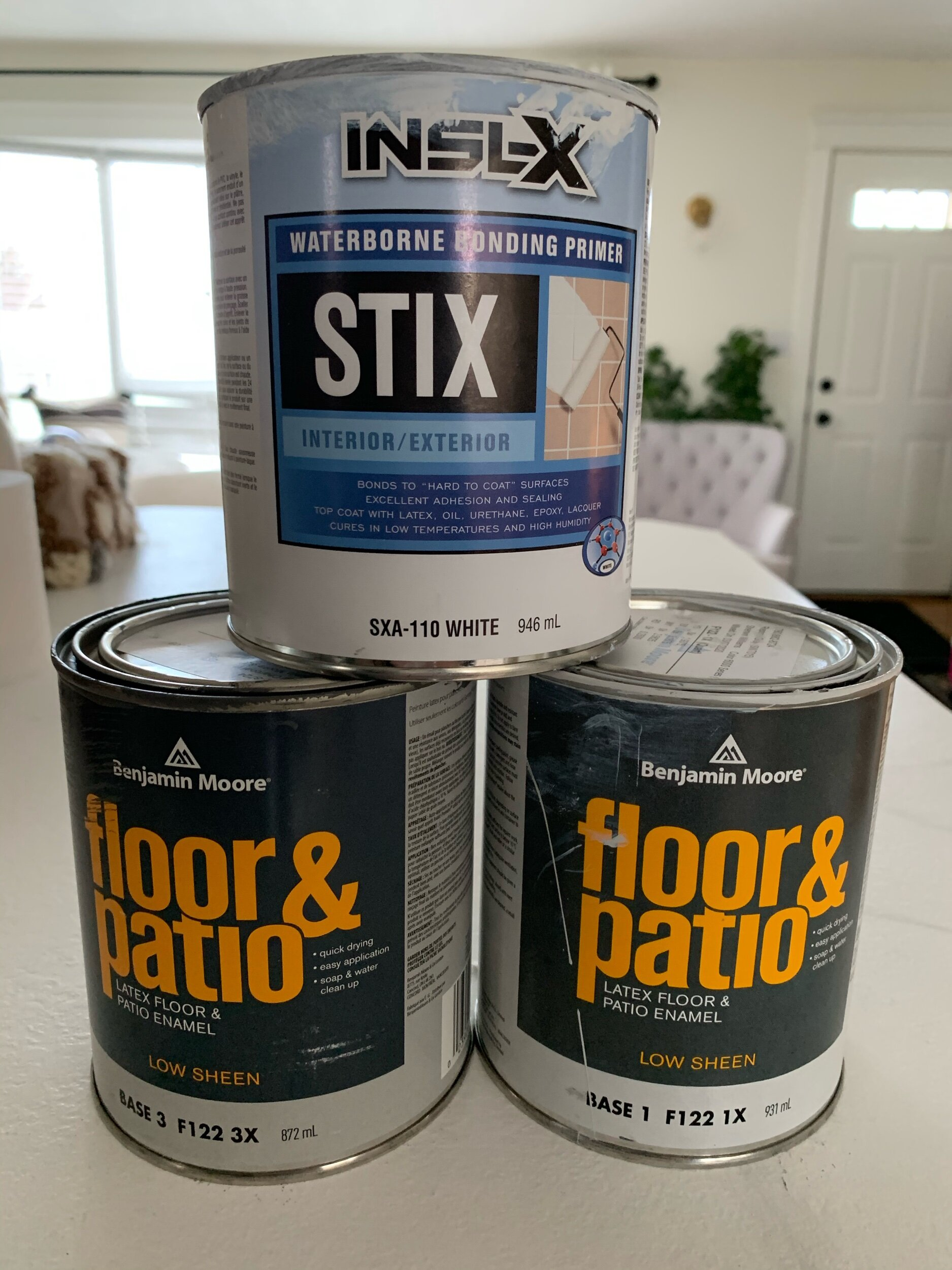 this is a photo of three paint cans, bonding primer and 2 cans of floor and patio paint