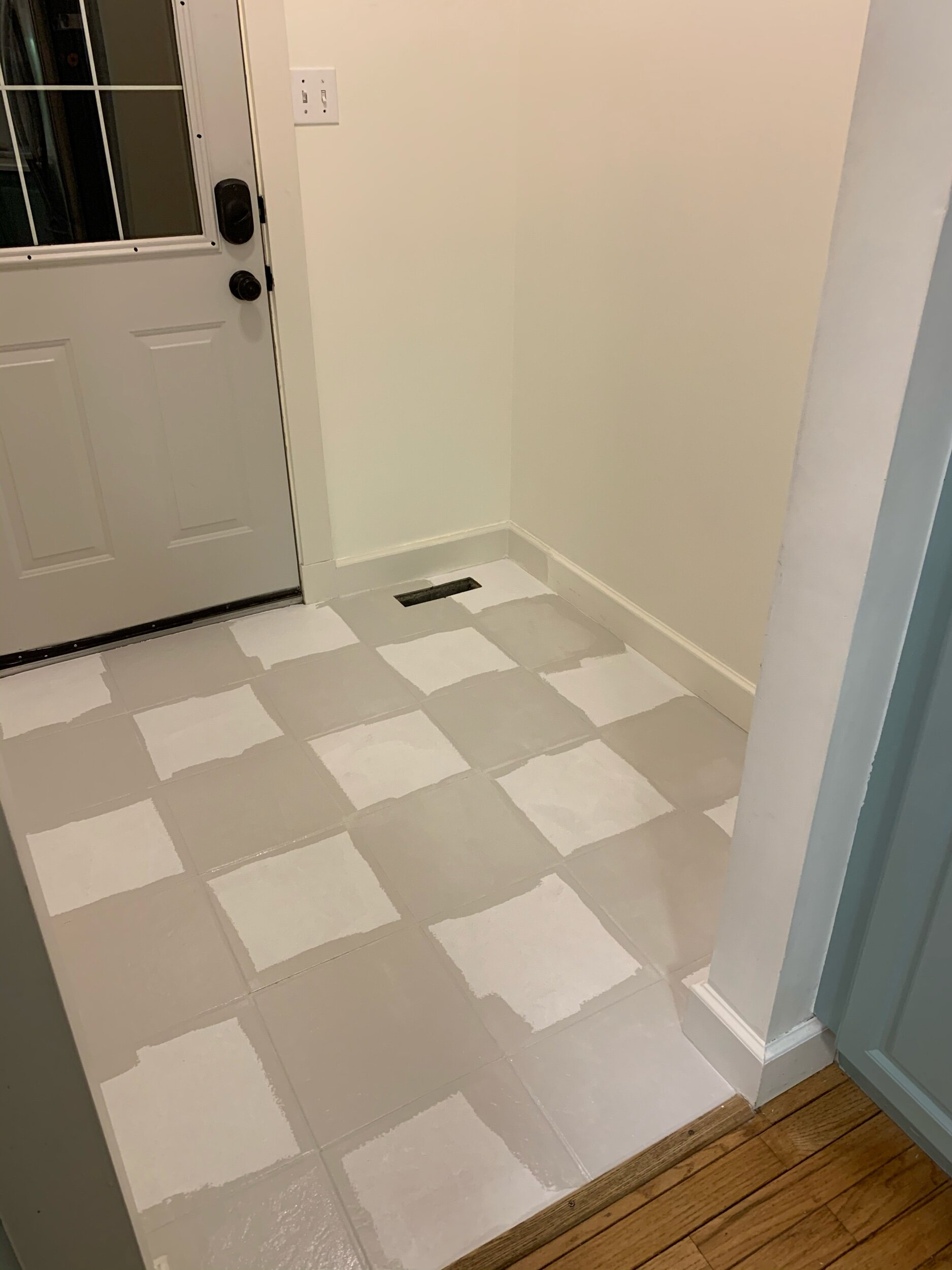 this is a photo of the beginning stages of painting tile floors in a checkerboard patter using repose grey by sherwin williams paint