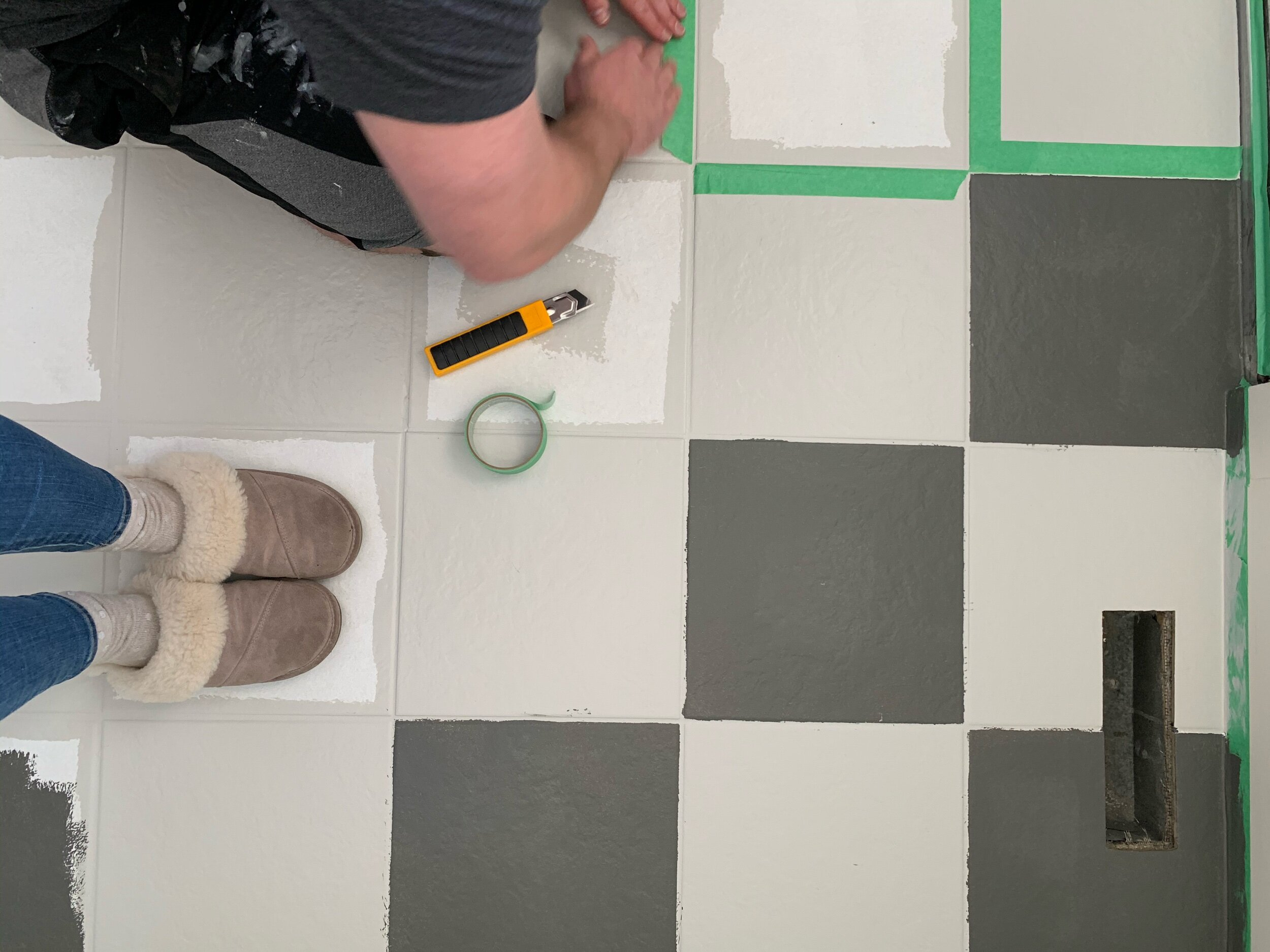 this is a photo of creating a checker board pattern with frog tape on tile floors with repose grey paint and kendall charcoal paint