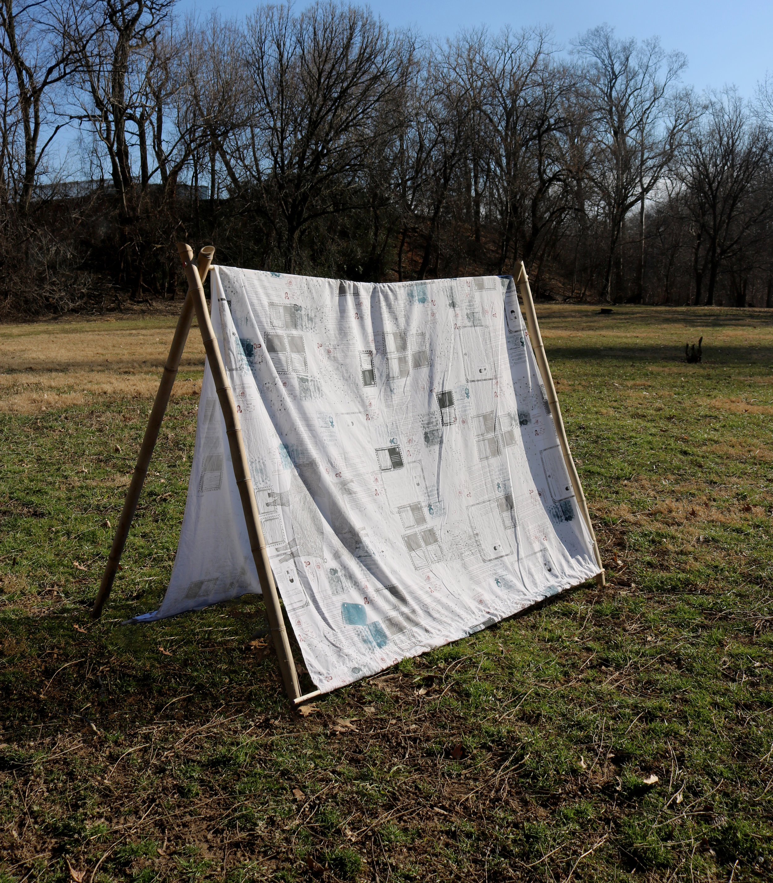 """To Build a Shelter , 32"""" x 72"""" x 58,""""2019  Silkscreened official government images + documents on repurposed bedsheet, a-frame tent handcrafted from foraged & dried bamboo poles."""
