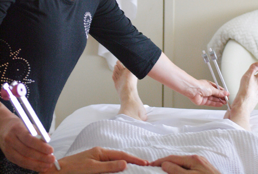 Acupuncturist using tuning fork therapy on patient