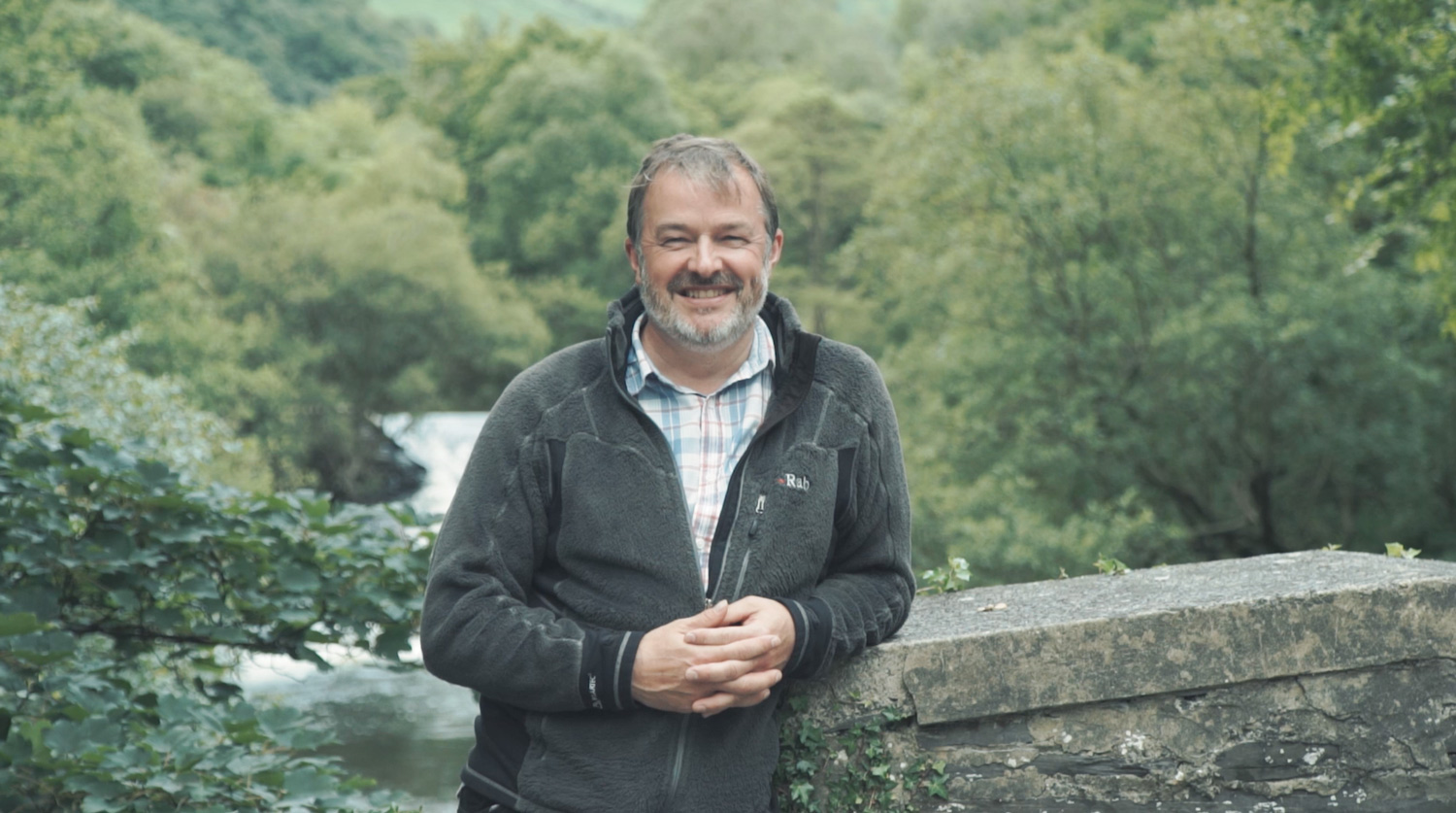 white middle aged man stands on bridge overlooking a river