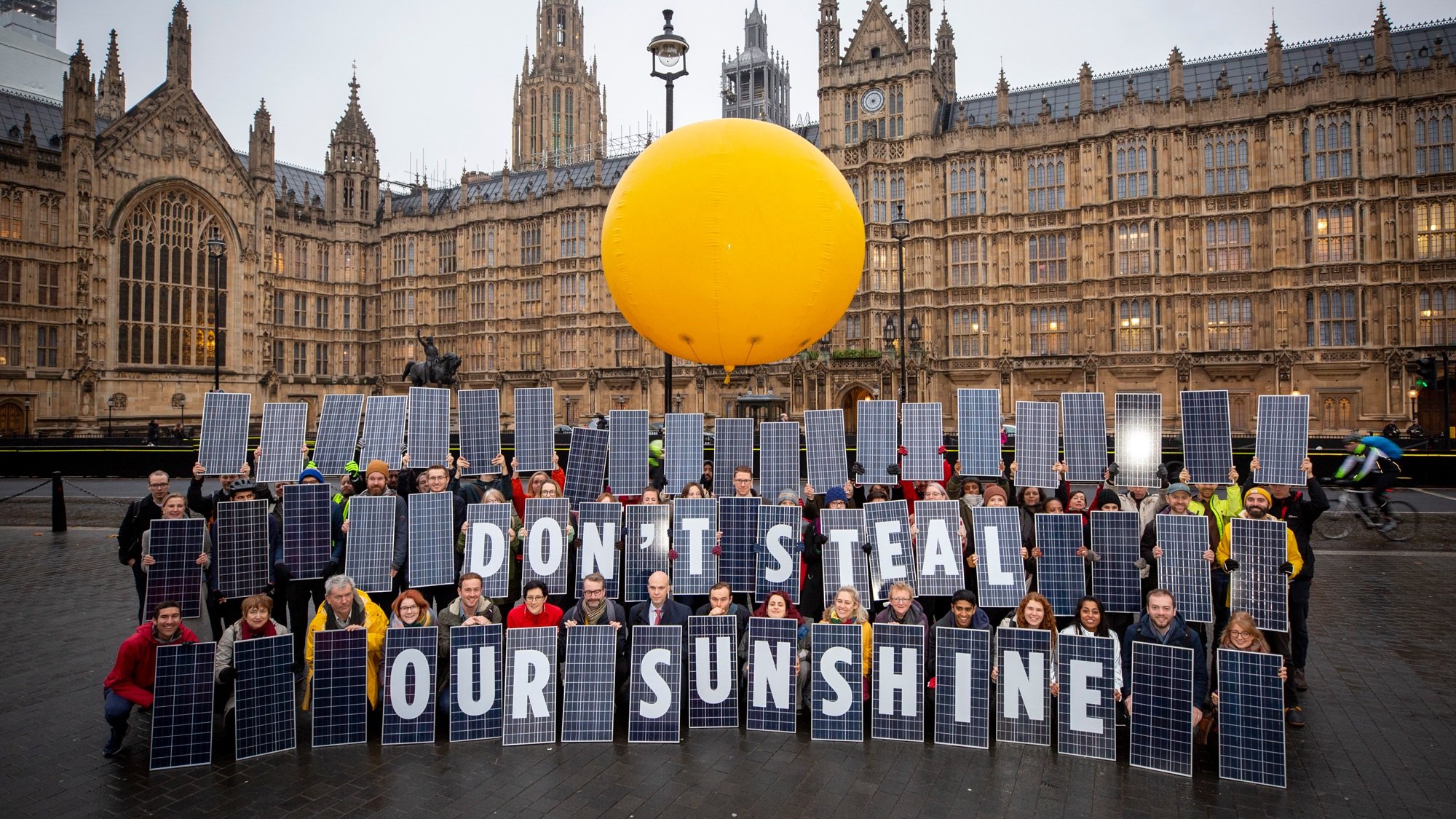 people outside houses of parliament hold up solar panels with 'don't steal our sunshine' written on them. A large orange ball floats above them.
