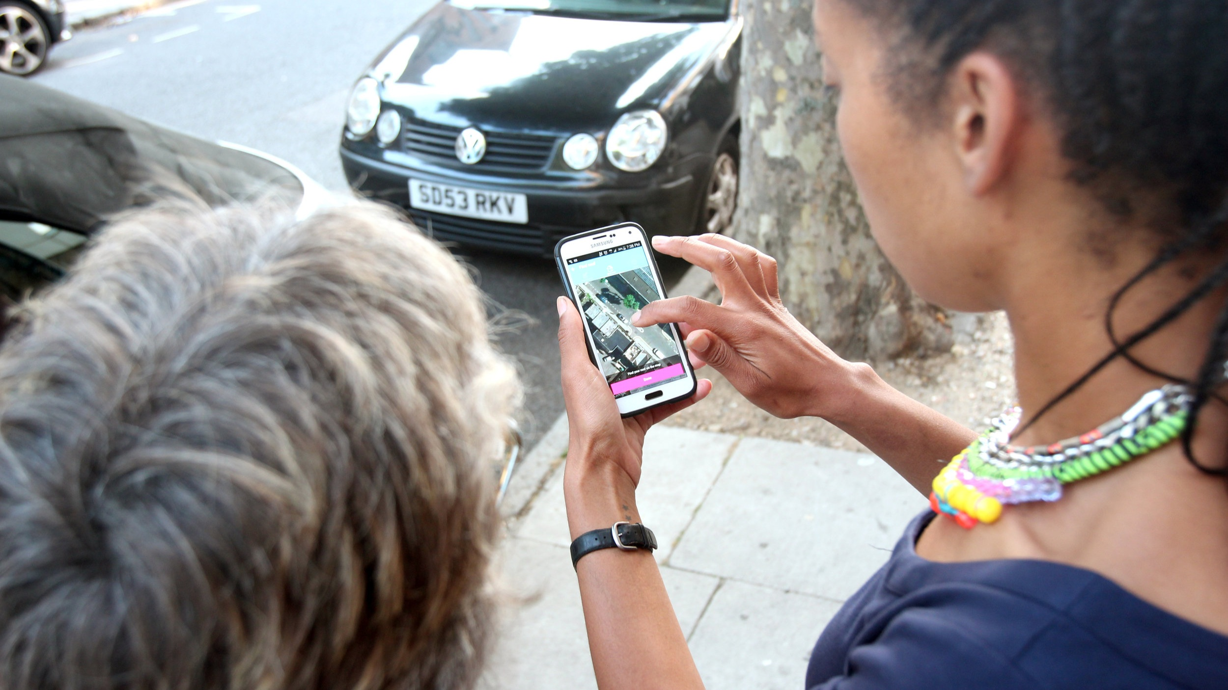 young woman uses app on phone as older woman looks on