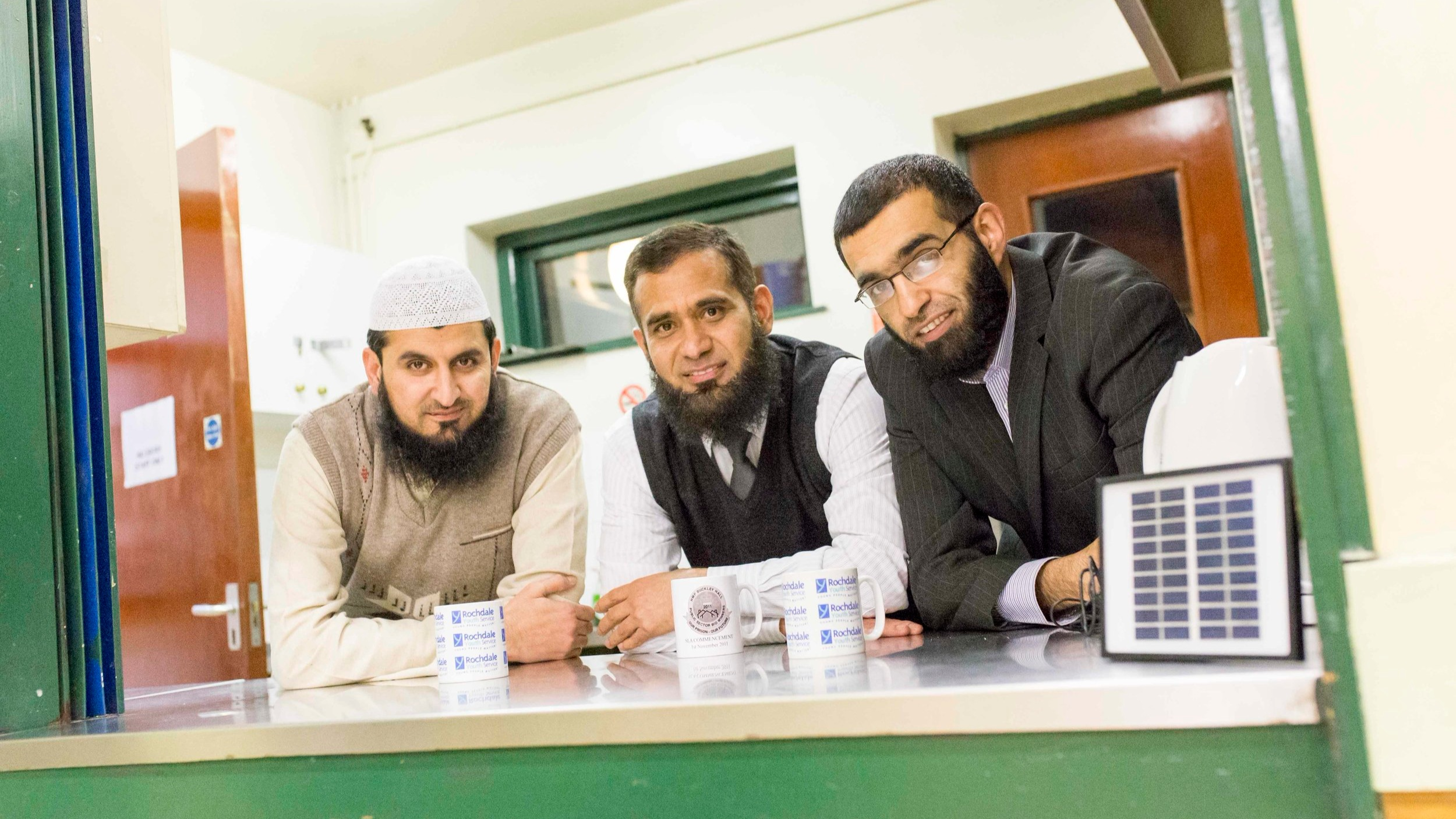 three asian men look over counter in community centre. they each have a mug of tea