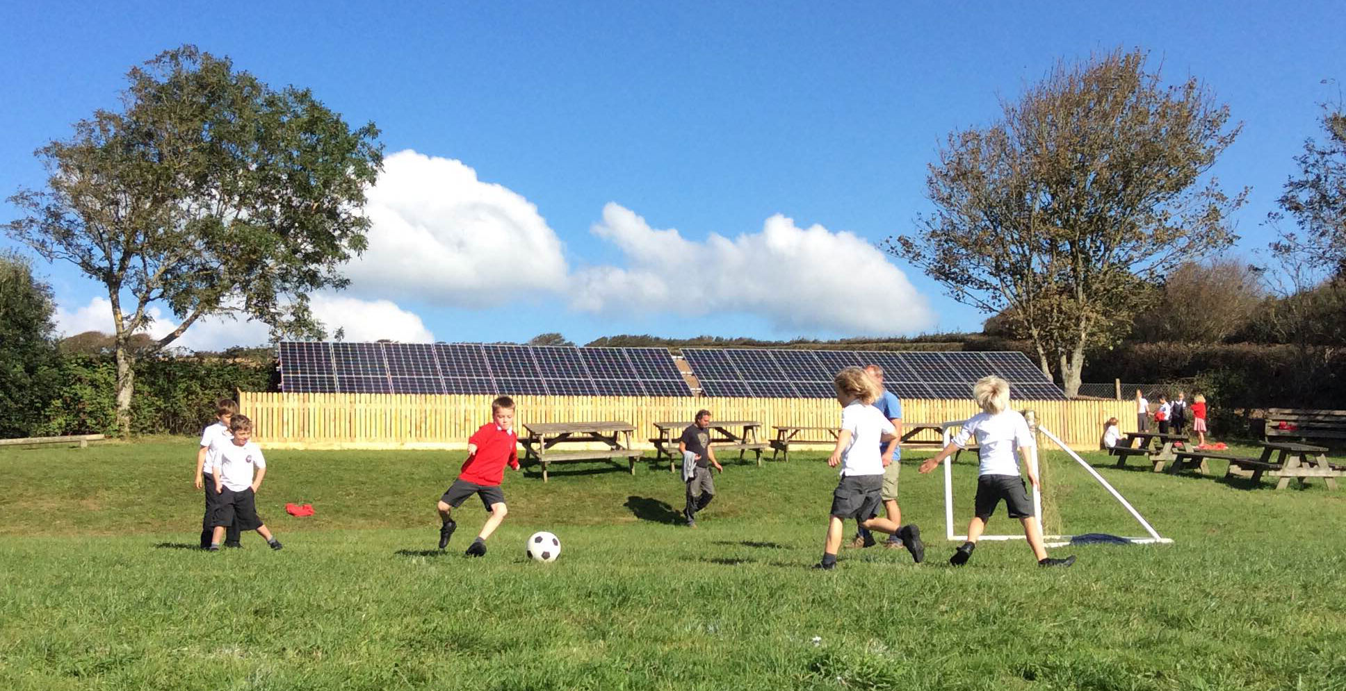 children in school uniform play football in front of solar panels