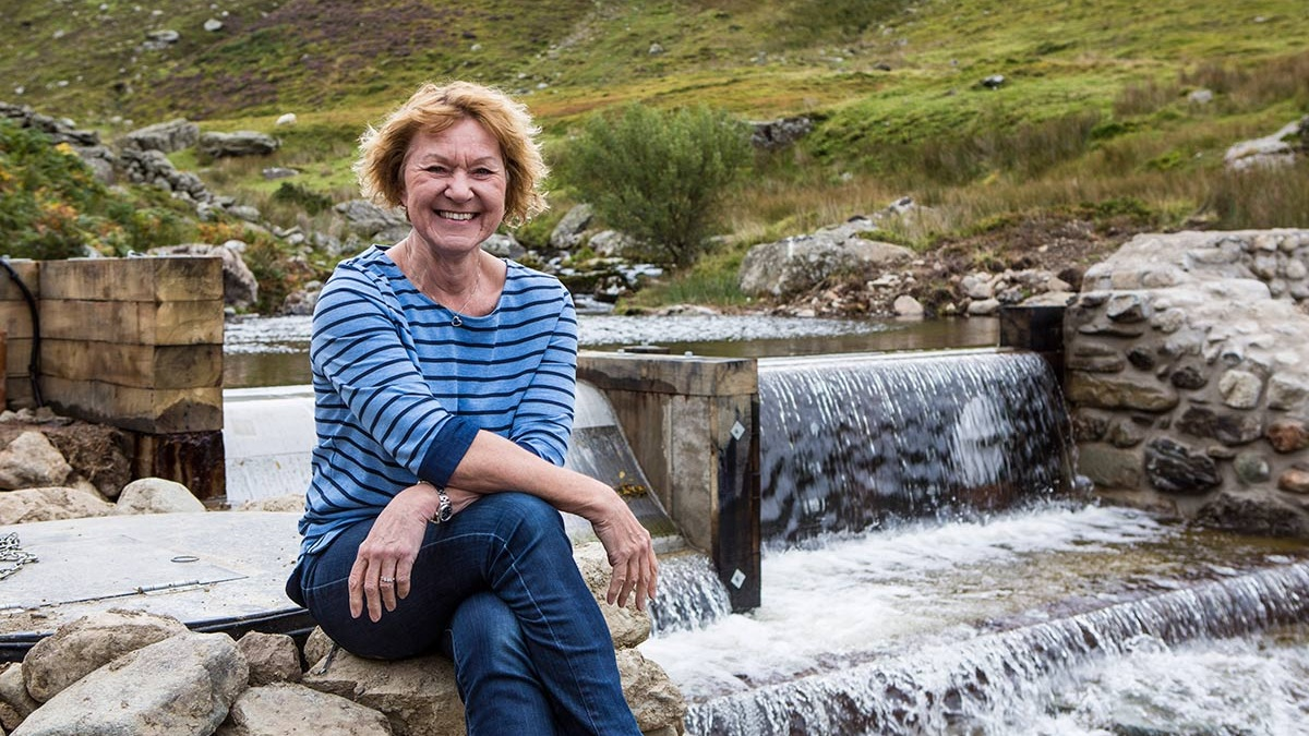 older white woman in stripy t-shirt sits on edge of weir