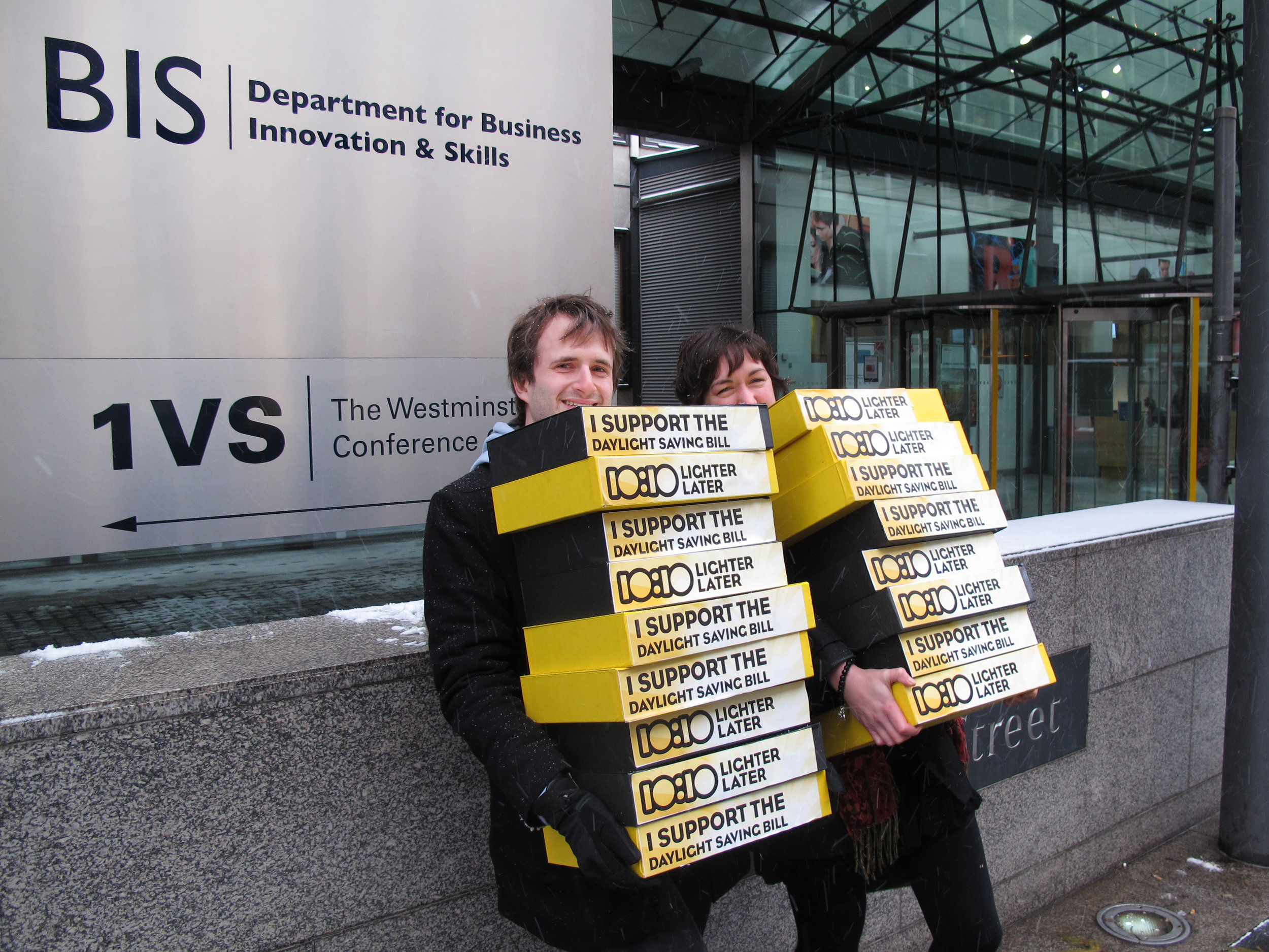 two people deliver letters in yellow boxes to BIS. Boxes read 'i support the daylight saving bill'