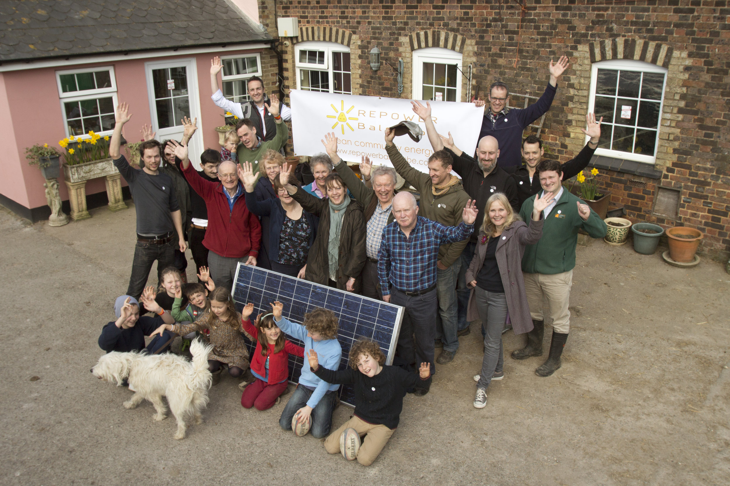 balcombe residents and dog hold 'repower balcombe' sign and cheer