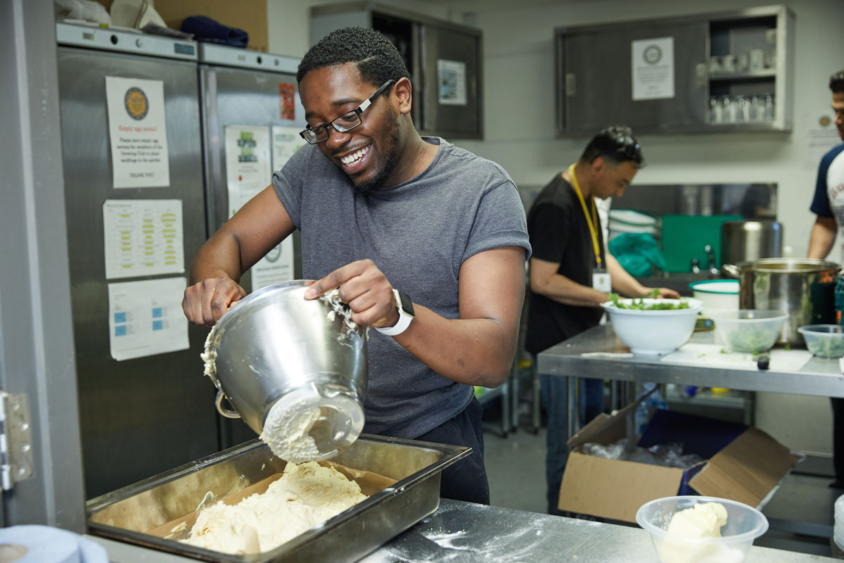 young black man in grey t-shirt serves mashed potato