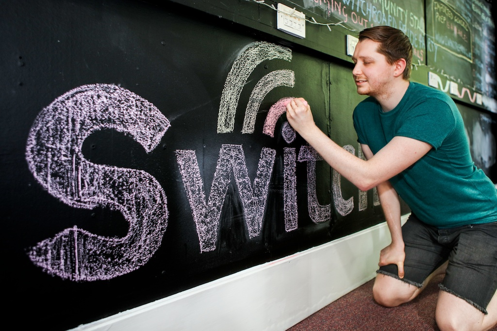 young white man in green shirt does chalk drawing on wall. It reads 'switch'. the rest is obscured