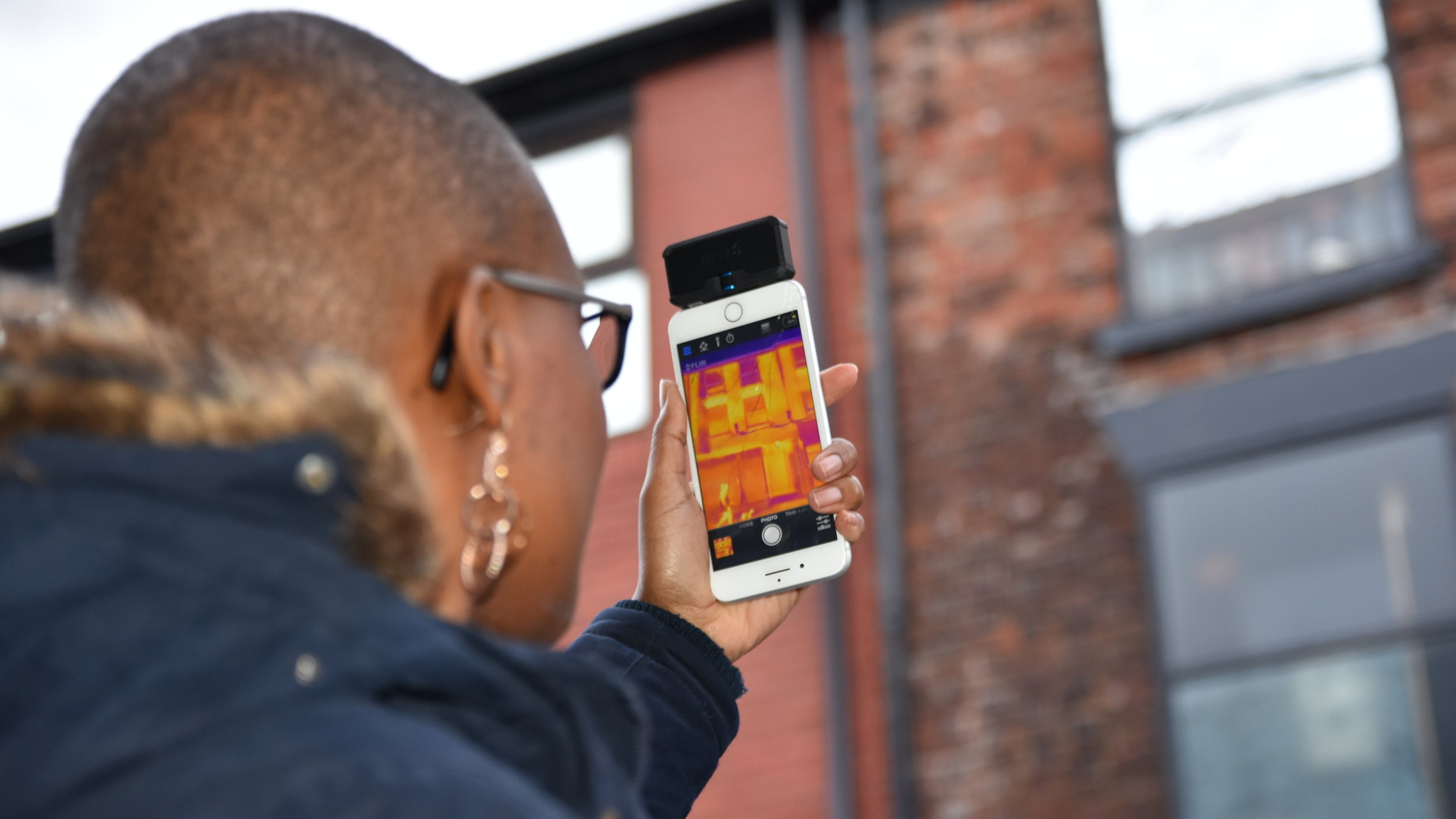 woman using heat camera attached to phone. Link: Clean heat