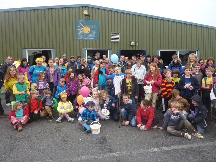 big group of smiling children and adults in front of school. Some have balloons and collection buckets.