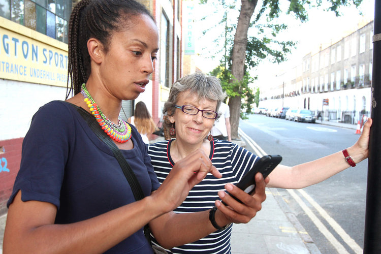 Feimatta looks at phone as an older white woman in a stripy t-shirt looks on.