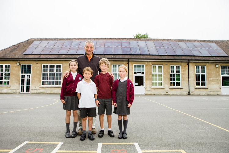 Richard stands in school playground with four children. There are solar panels on the roof.