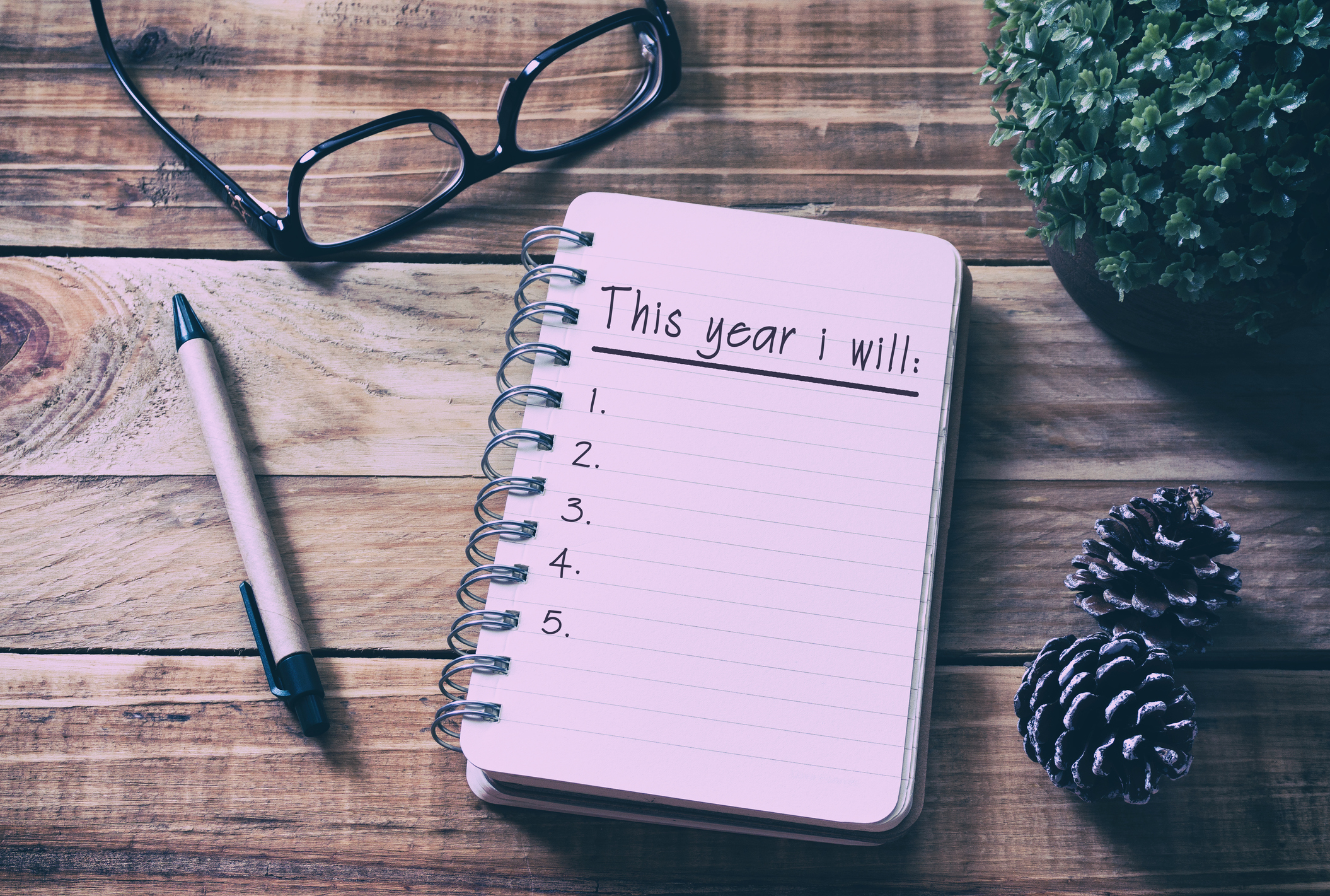 """Notebook with """"This year I will:"""" written on it followed by the numbers one through five."""