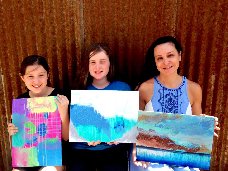 A mother and daughters painting class.