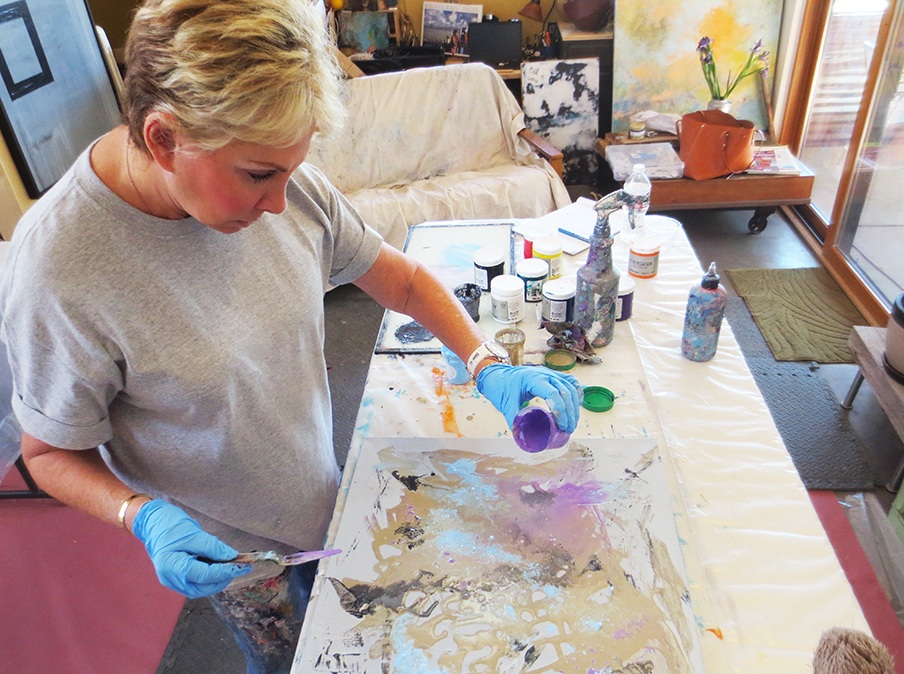 A student using pouring medium that she just learned to make in the 3-day abstract painting intensive.