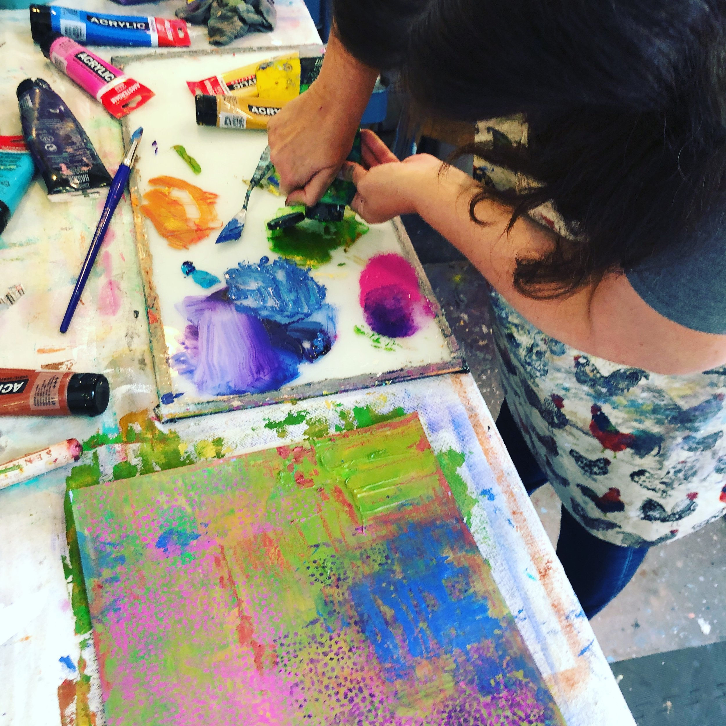 A student pushing the boundaries in her process by covering up areas with stencils and big blocks of color.