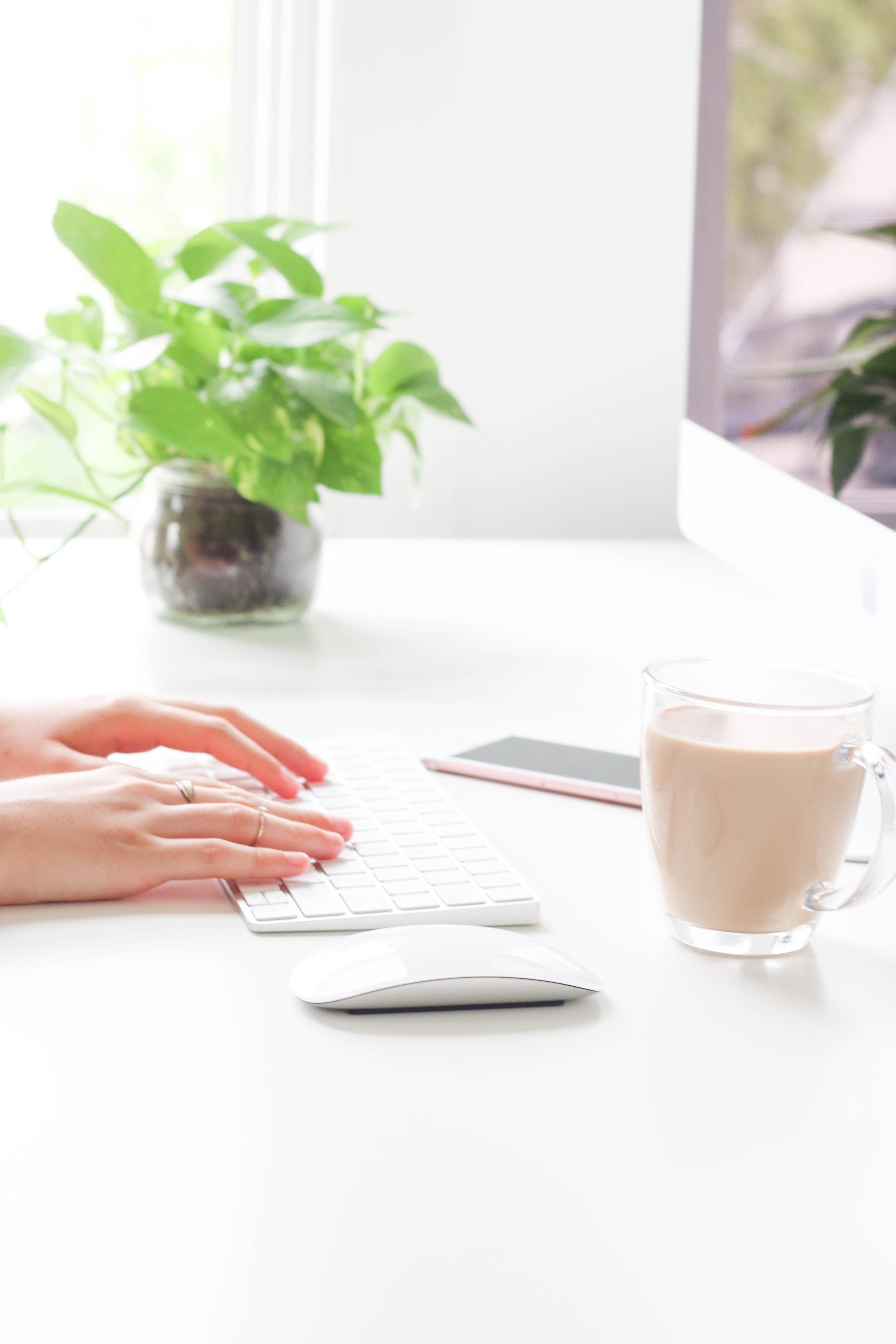 Woman typing on computer with coffee, plant, and phone.