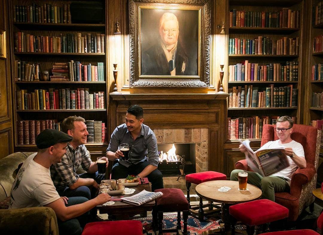 Four young men sitting by the fire with beer and food in the library at The Duke of Clarence bar in Sydney