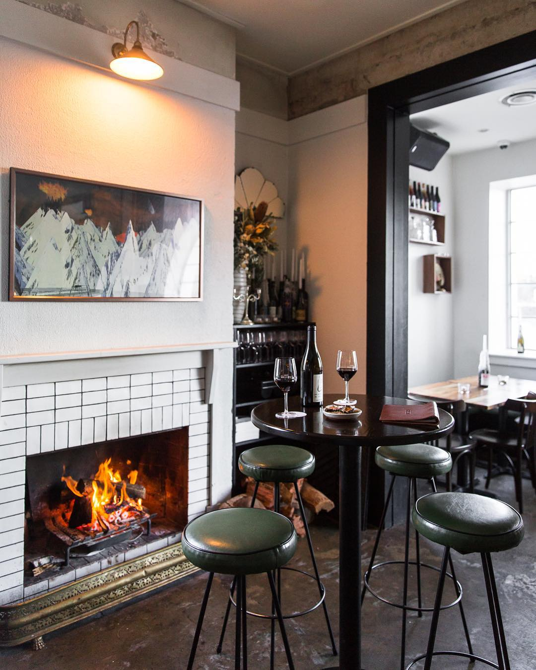 A bar table with a bottle and two glasses of red wine in front of the fireplace at Bar Rochford in Canberra