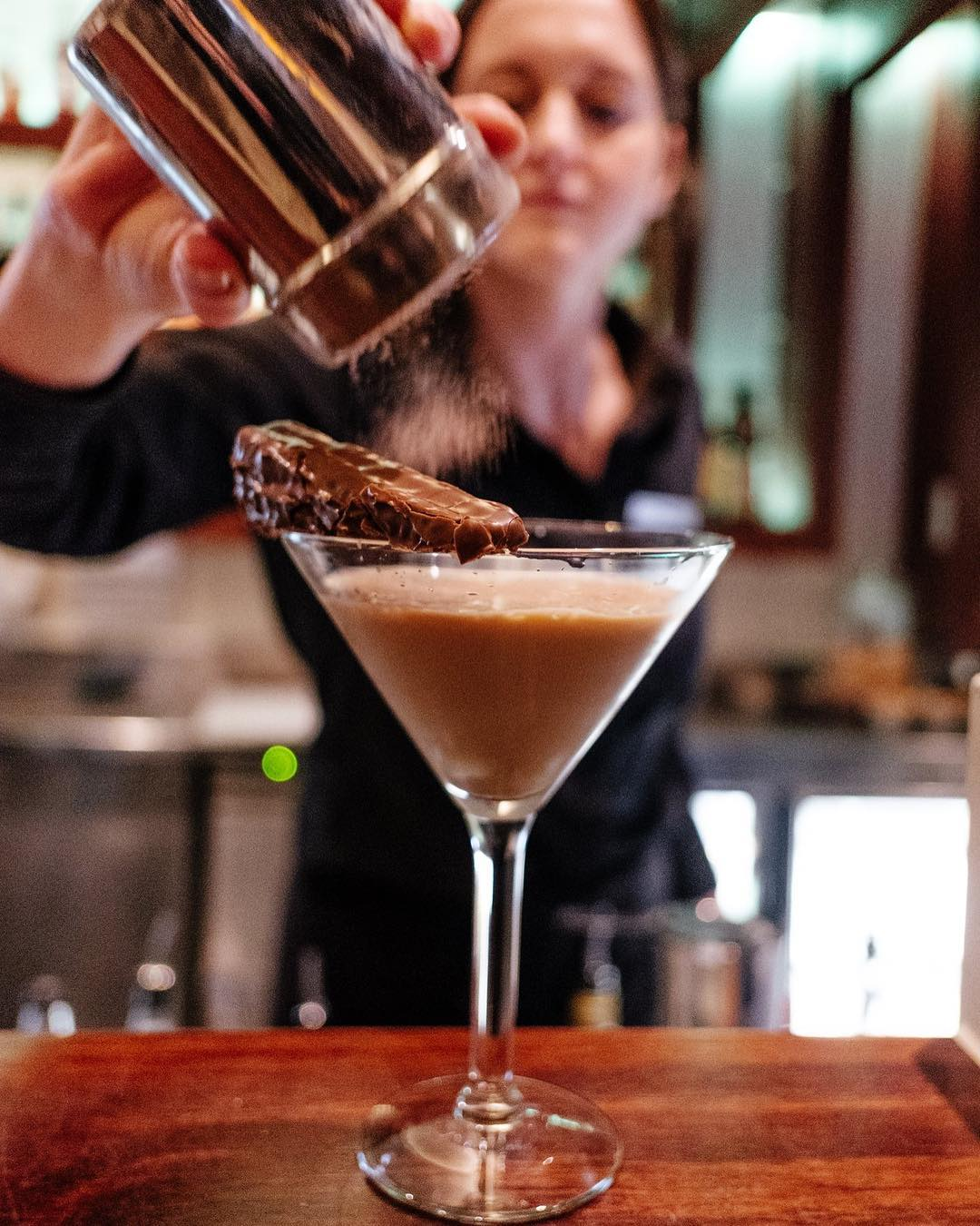 Female bartender dusting cocoa powder on a Mars bar cocktail at a cosy bar in Melbourne