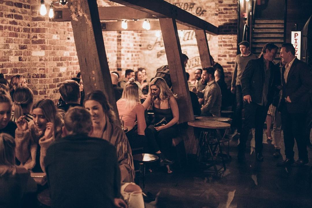 A group of about 20 people sitting at tables at Bank St Social, the underground Adelaide bar