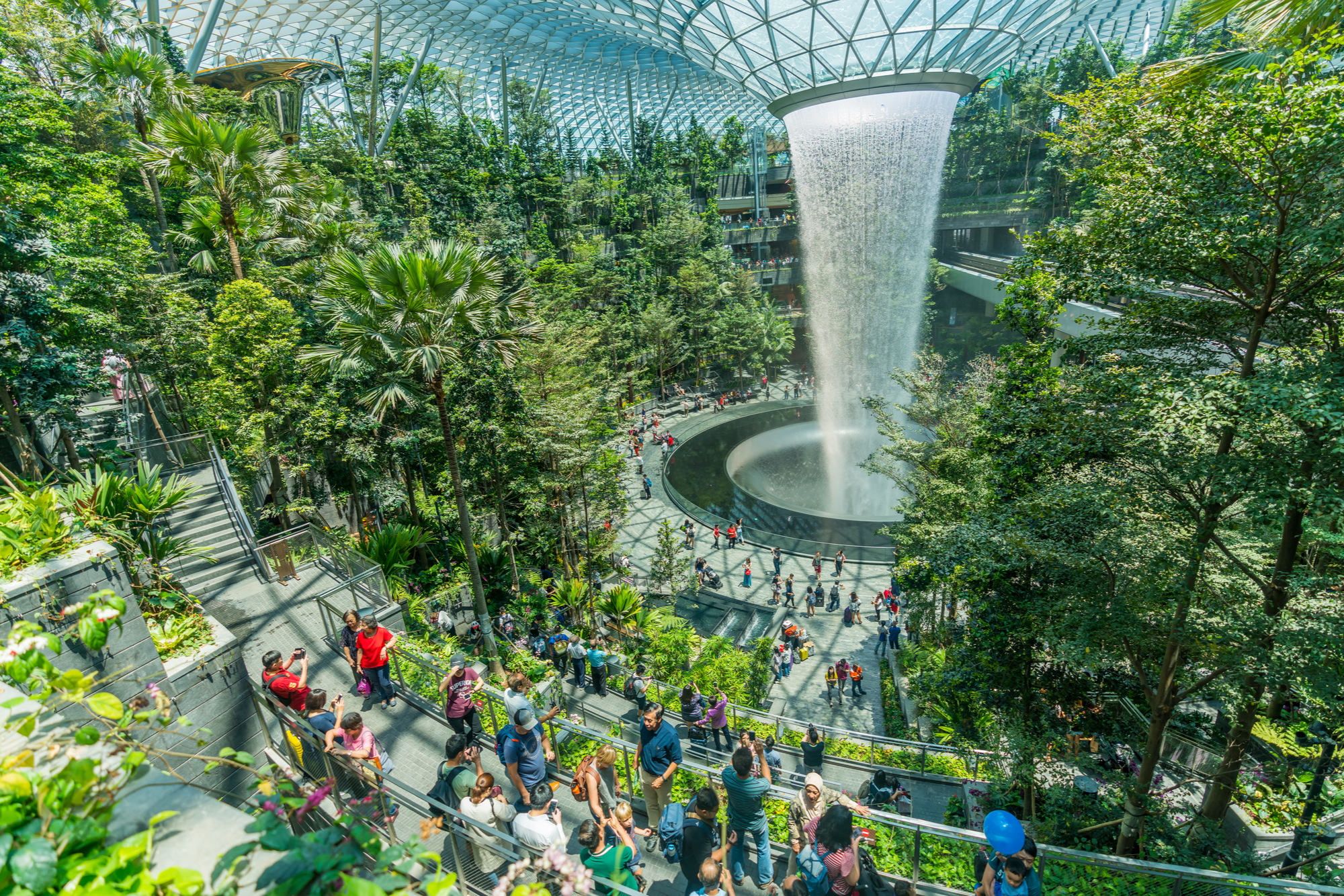 Passengers looking at the Rain Vortex located inside the Jewel at Changi Airport during a stopover in Singapore