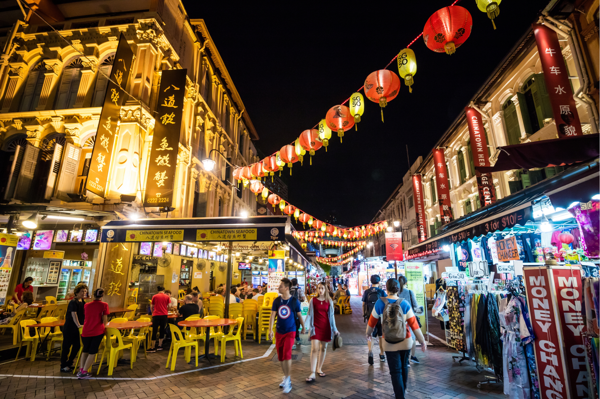 Chinatown at nighttime with lanterns criss-crossing a street filled with shoppers and restaurant-goers