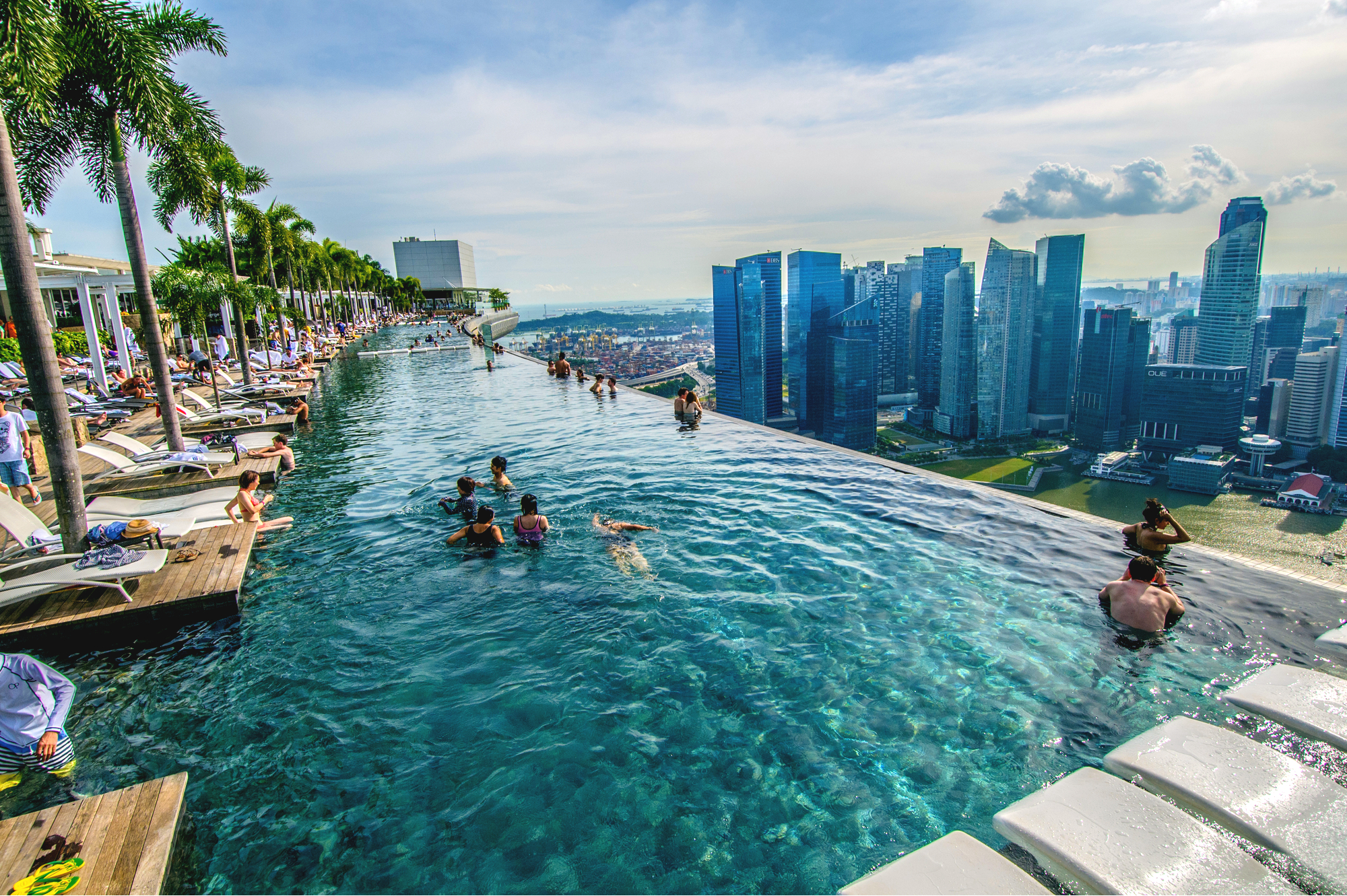 People swimming in the rooftop infinity pool at Marina Bay Sands, overlooking the Singapore skyline